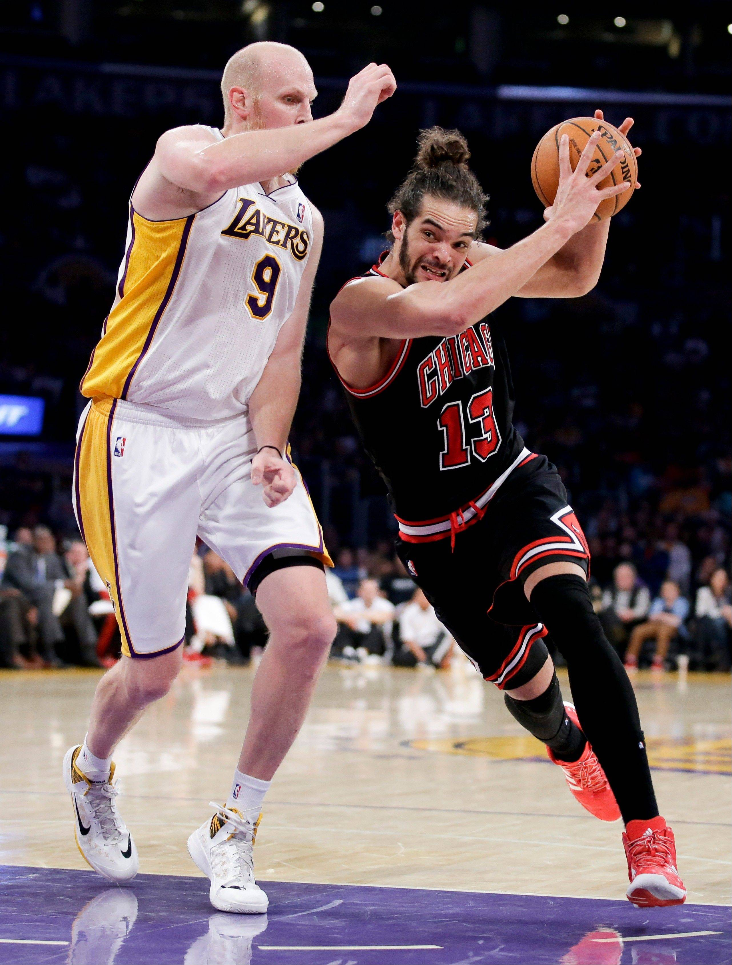 The Bulls' Joakim Noah drives around the Lakers' Chris Kaman during the second half Sunday.