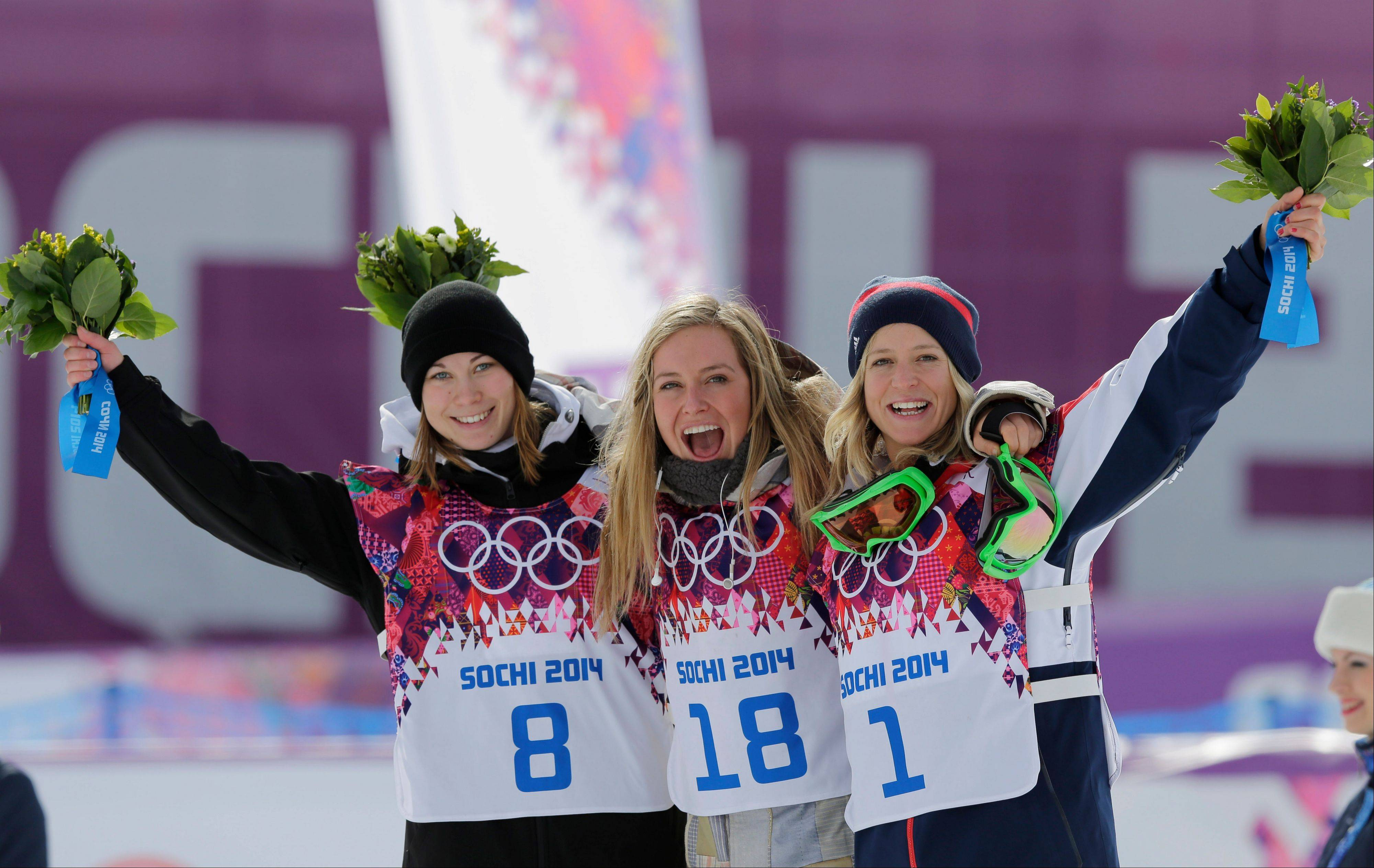 Jamie Anderson of the United States, center, celebrates with silver medalist Enni Rukajarvi of Finland, left, and bronze medalist Jenny Jones of Britain, after Anderson won the women's snowboard slopestyle final at the 2014 Winter Olympics, Sunday, Feb. 9, 2014, in Krasnaya Polyana, Russia.