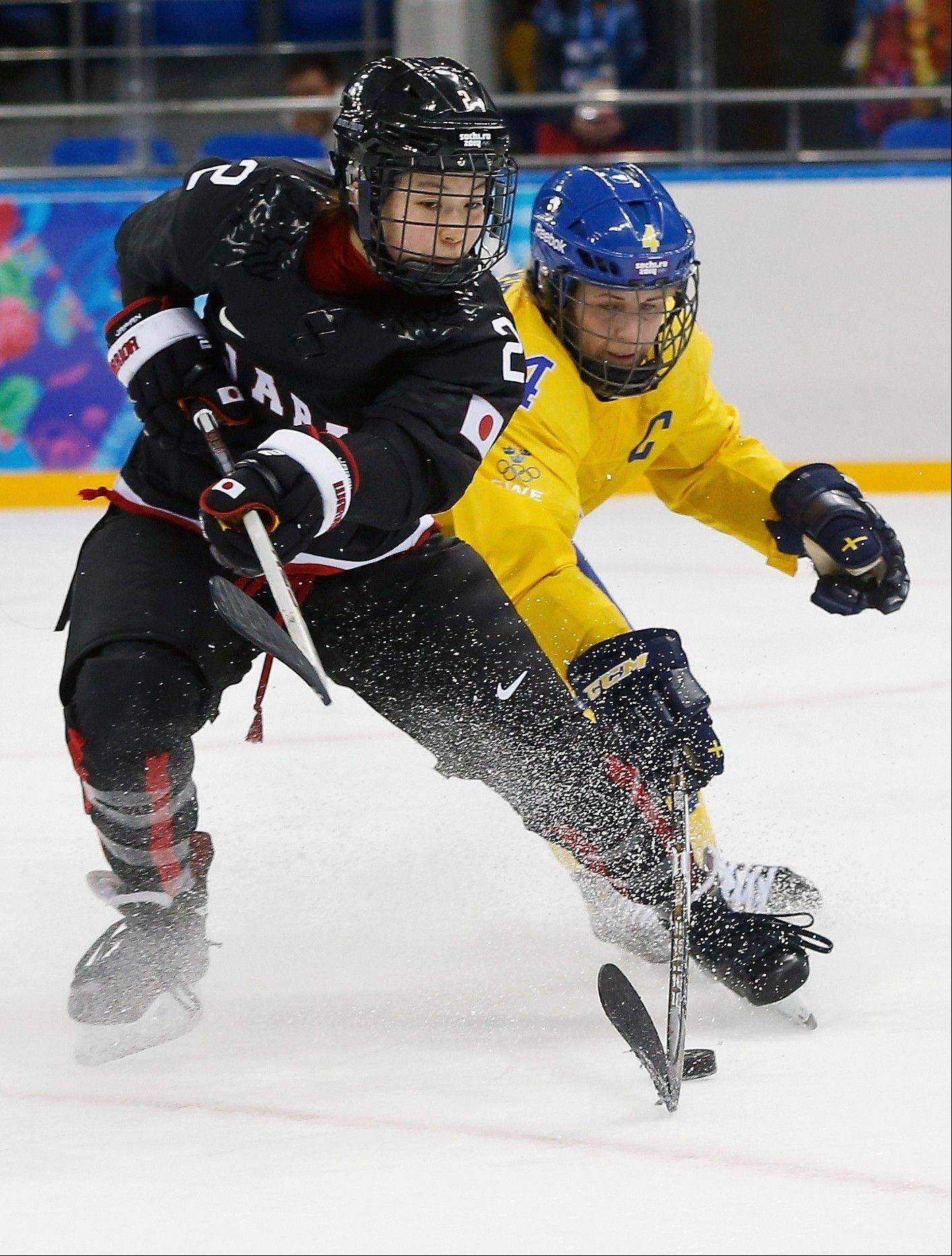 Shiori Koike of Japan and Jenni Asserholt of Sweden battle for control of the puck during the third period of the 2014 Winter Olympics women's ice hockey game at Shayba Arena, Sunday, Feb. 9, 2014, in Sochi, Russia.
