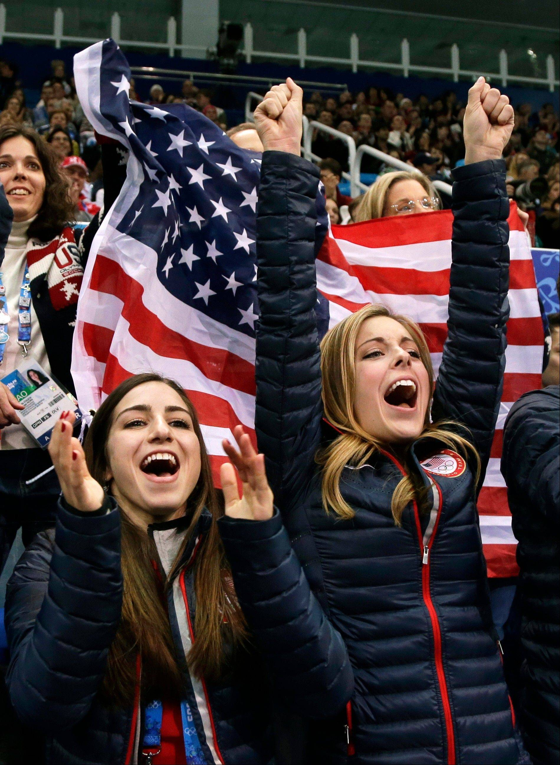 Marissa Castelli, left, and Ashley Wagner cheer for Jason Brown of the United States as he compete in the men's team free skate figure skating competition at the Iceberg Skating Palace during the 2014 Winter Olympics, Sunday, Feb. 9, 2014, in Sochi, Russia.