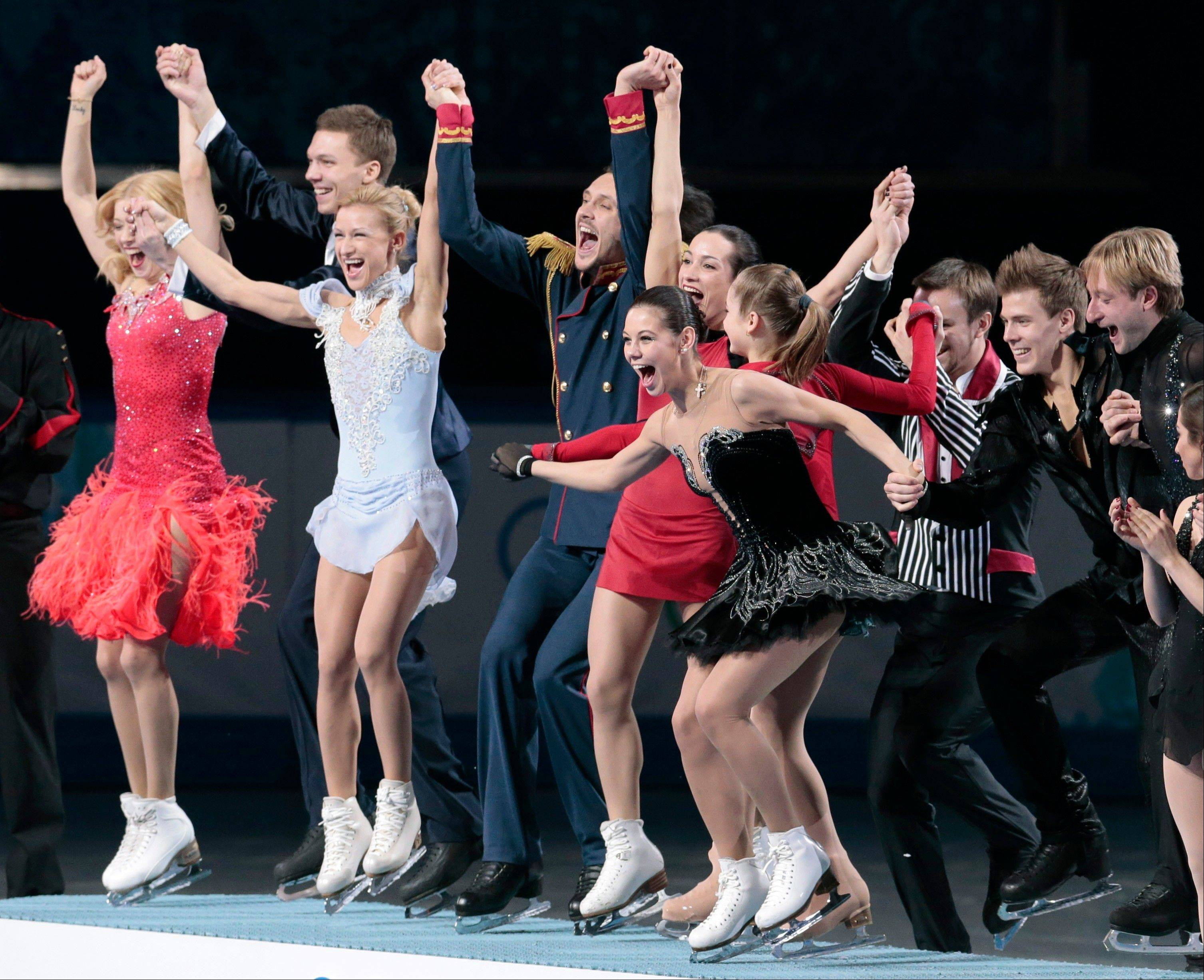 The Russian team wave to spectators as they stand on the podium during the flower ceremony after placing first in the team figure skating competition at the Iceberg Skating Palace during the 2014 Winter Olympics, Sunday, Feb. 9, 2014, in Sochi, Russia.