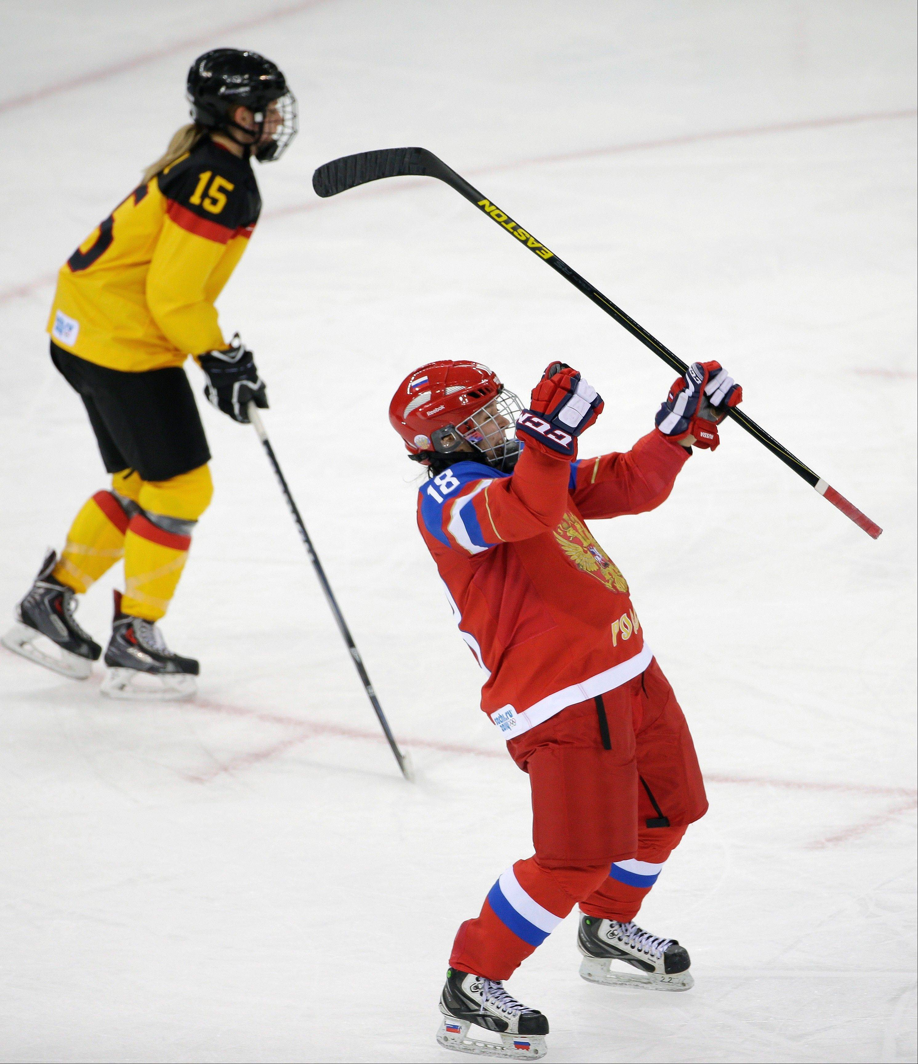 Olga Sosina of Russia celebrates her second goal against Germany as Andrea Lanzl of Germany skates by during the third period of the 2014 Winter Olympics women's ice hockey game at Shayba Arena, Sunday, Feb. 9, 2014, in Sochi, Russia.