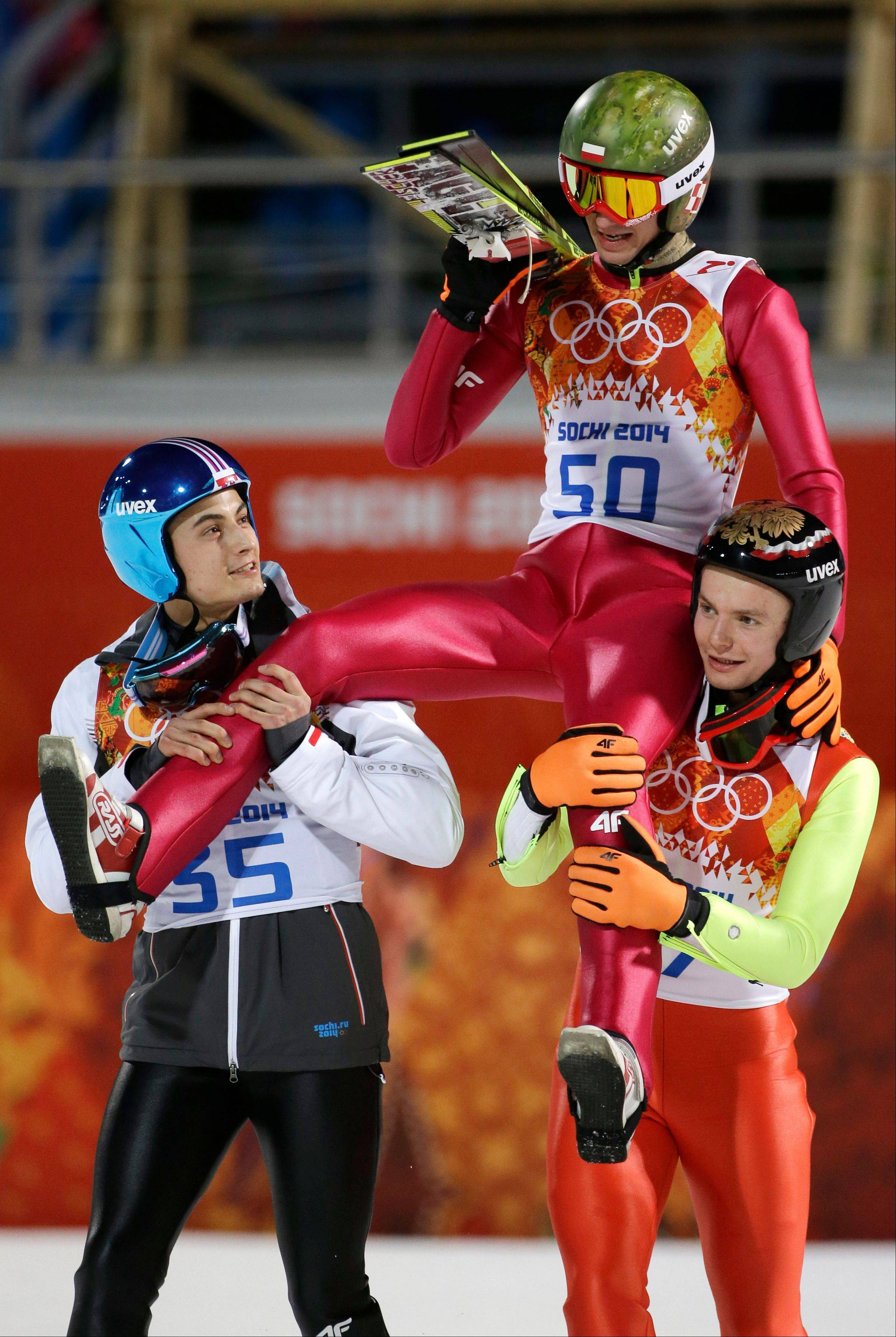 Poland's Kamil Stoch, center, is carried by his teammates Jan Ziobro, right, and Maciej Kot, left, after winning the gold in the men's normal hill ski jumping final at the 2014 Winter Olympics, Sunday, Feb. 9, 2014, in Krasnaya Polyana, Russia.