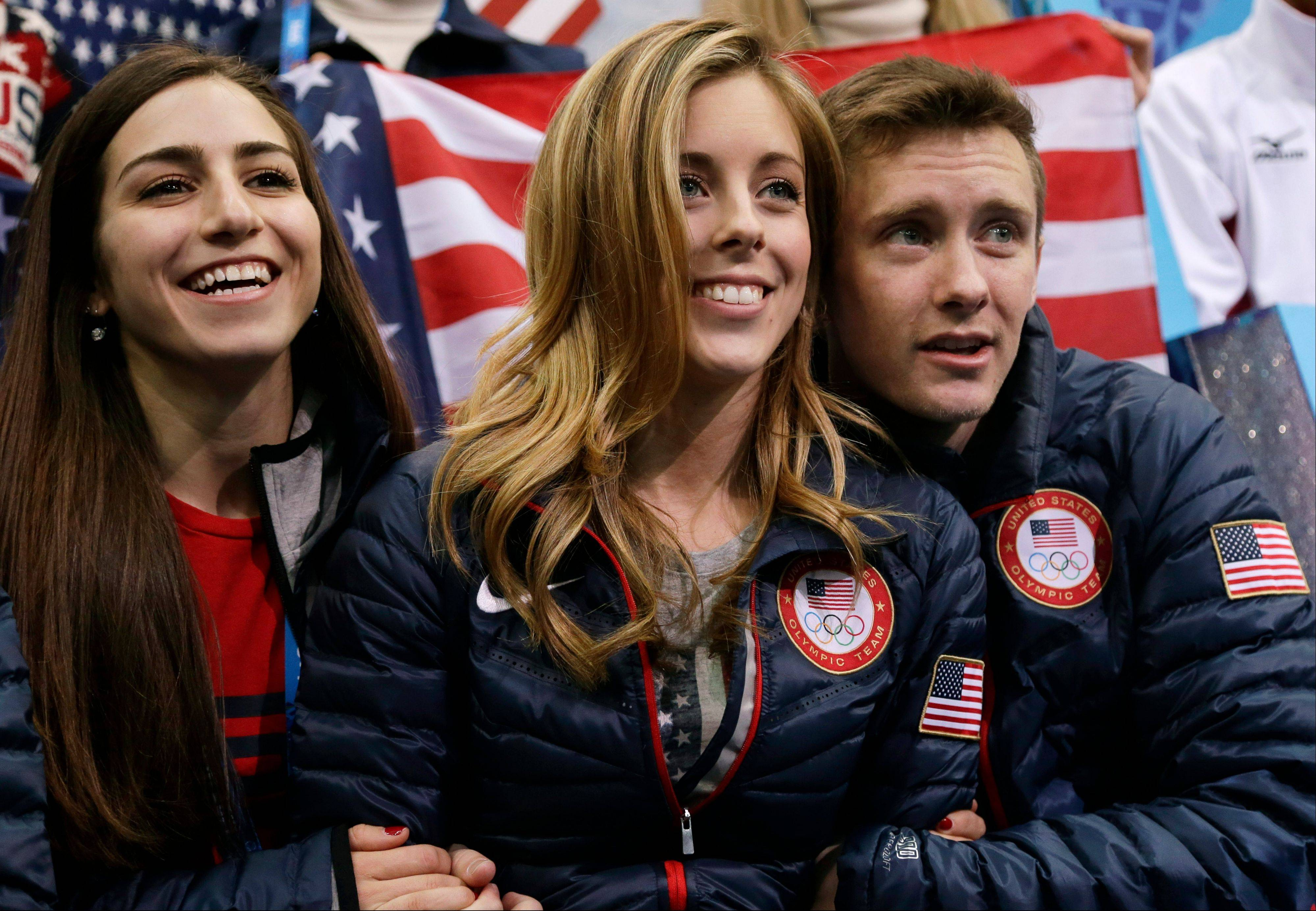 From left, Marissa Castelli, Ashley Wagner and Jeremy Abbott watch Jason Brown of the United States compete in the men's team free skate figure skating competition at the Iceberg Skating Palace during the 2014 Winter Olympics, Sunday, Feb. 9, 2014, in Sochi, Russia.
