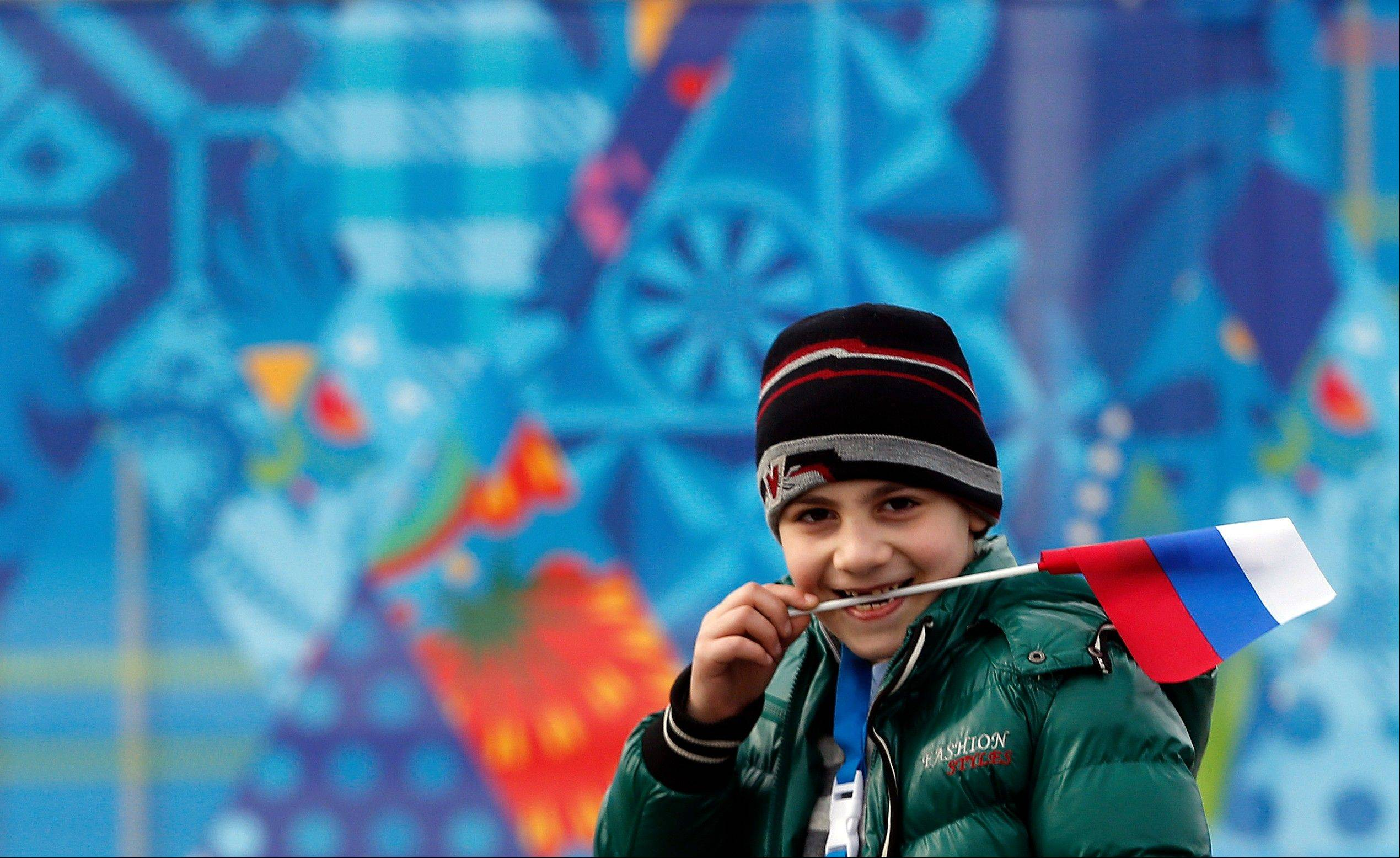 A boy holds a Russian flag in his mouth during the 2014 Winter Olympics, Sunday, Feb. 9, 2014, in Sochi, Russia.