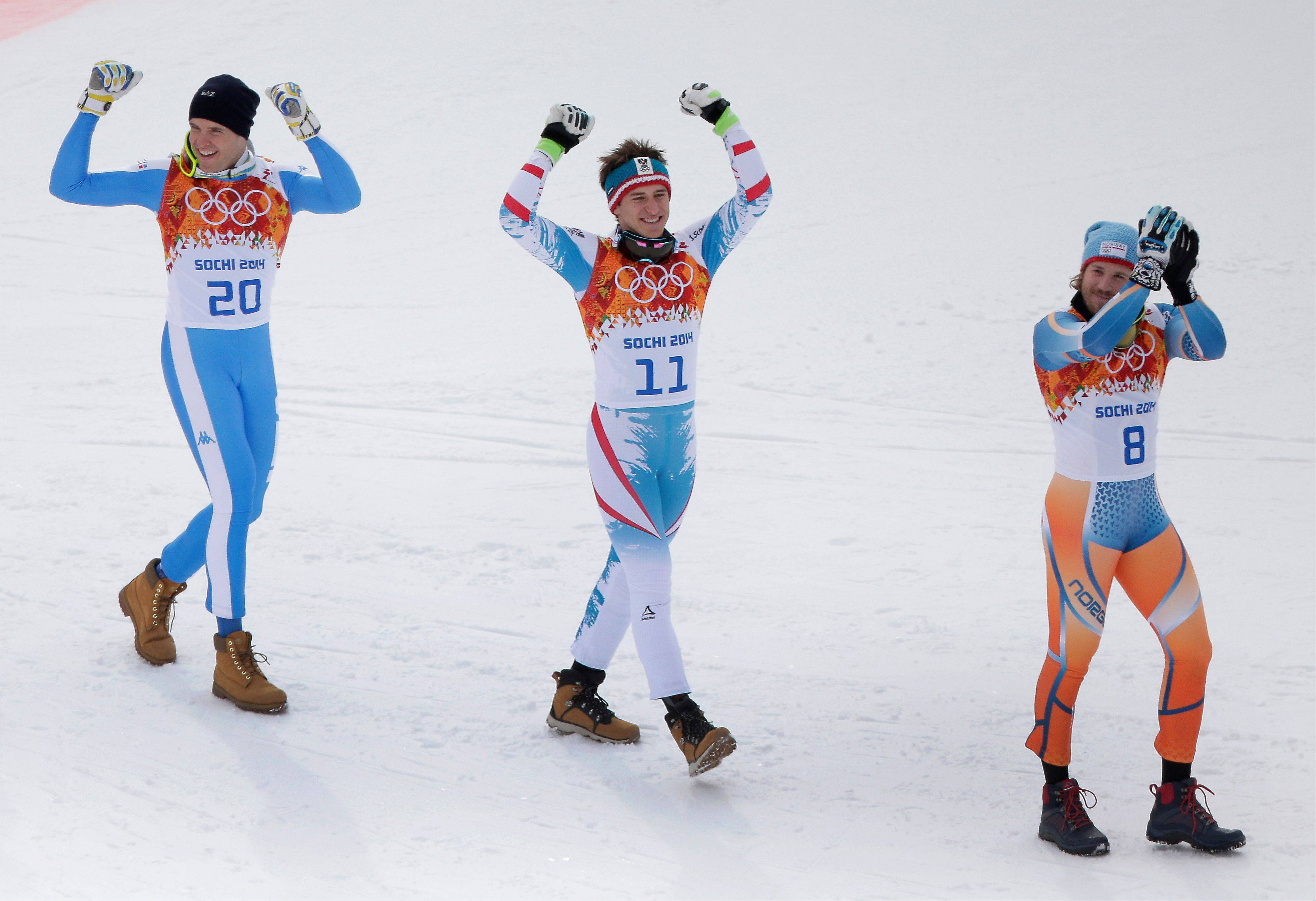 Austria's Matthias Mayer (11), Italy's Christof Innerhofer (20, and Norway's Kjetil Jansrud (8) walk to the flower ceremony after finishing the men's downhill event at the 2014 Winter Olympics, Sunday, Feb. 9, 2014, in Krasnaya Polyana, Russia.