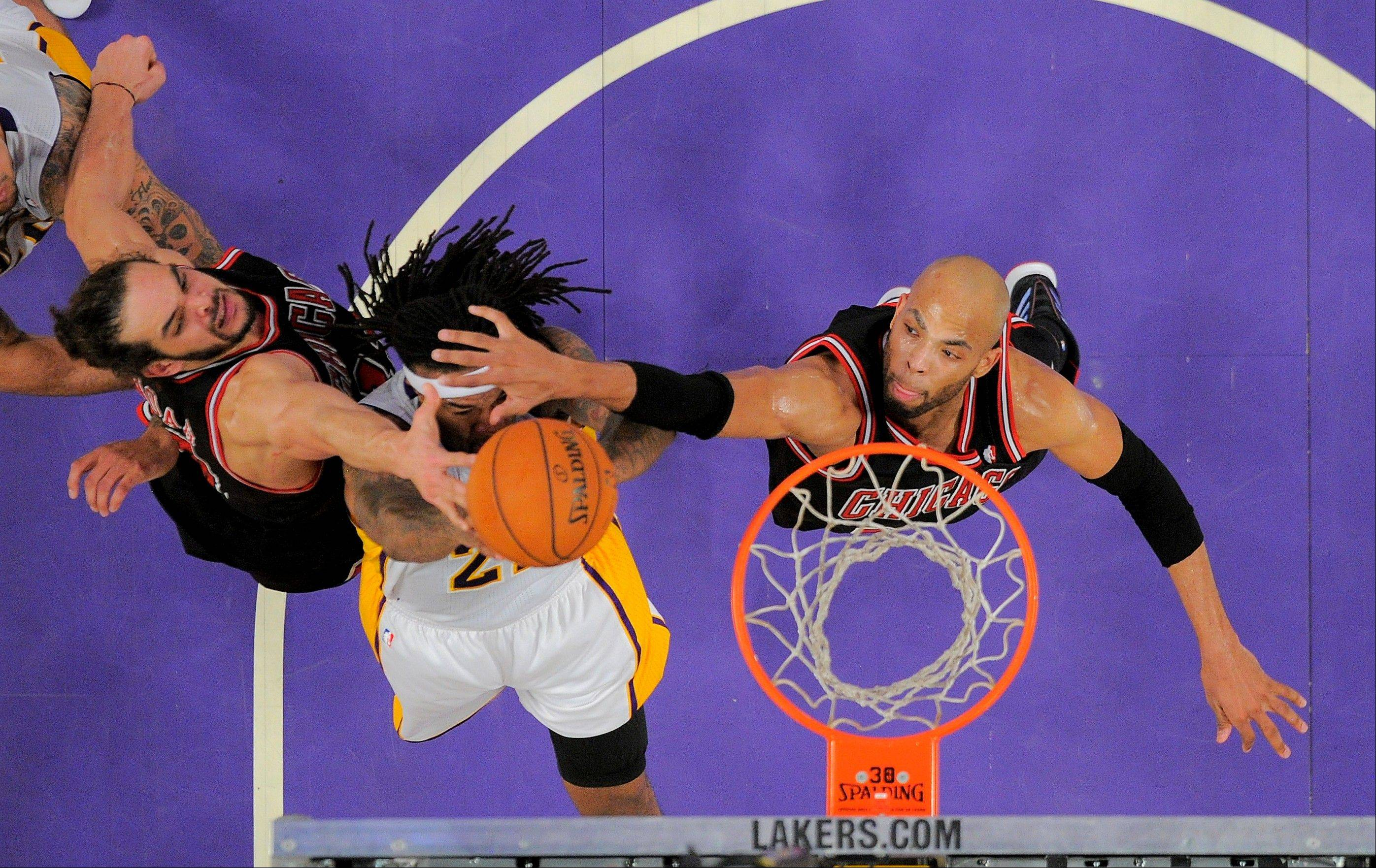 Los Angeles Lakers' Jordan Hill, middle, shoots between Chicago Bulls' Joakim Noah, left, and Taj Gibson during the first half of an NBA basketball game in Los Angeles, Sunday, Feb. 9, 2014.
