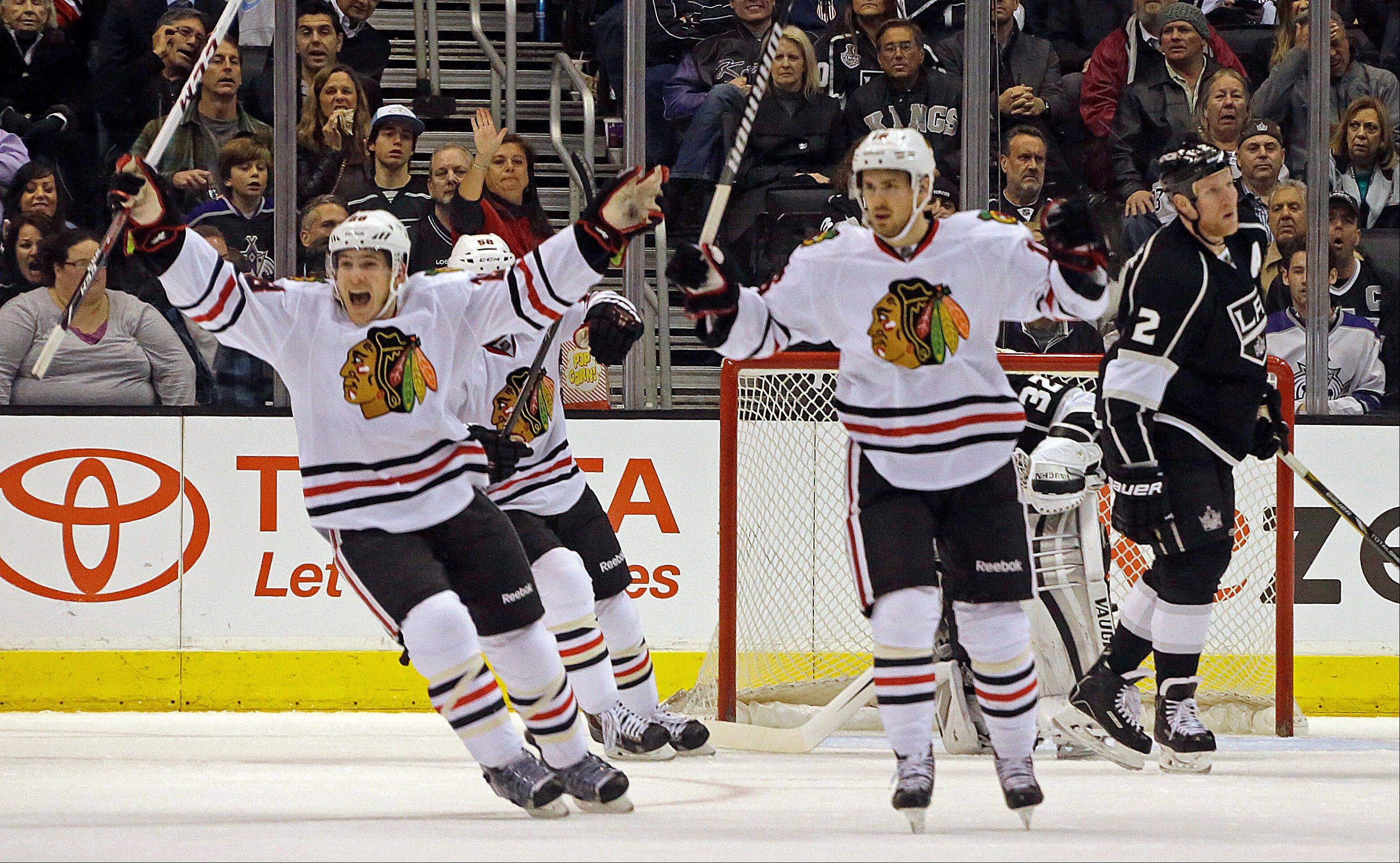 Blackhawks' Ben Smith (28), left, and defenseman Michael Kostka (6) celebrate a goal by Marcus Kruger, not shown, against Los Angeles Kings goalie Jonathan Quick (32) and defenseman Matt Greene (2) look on in the second period of an NHL hockey game in Los Angeles, Monday, Feb. 3, 2014.