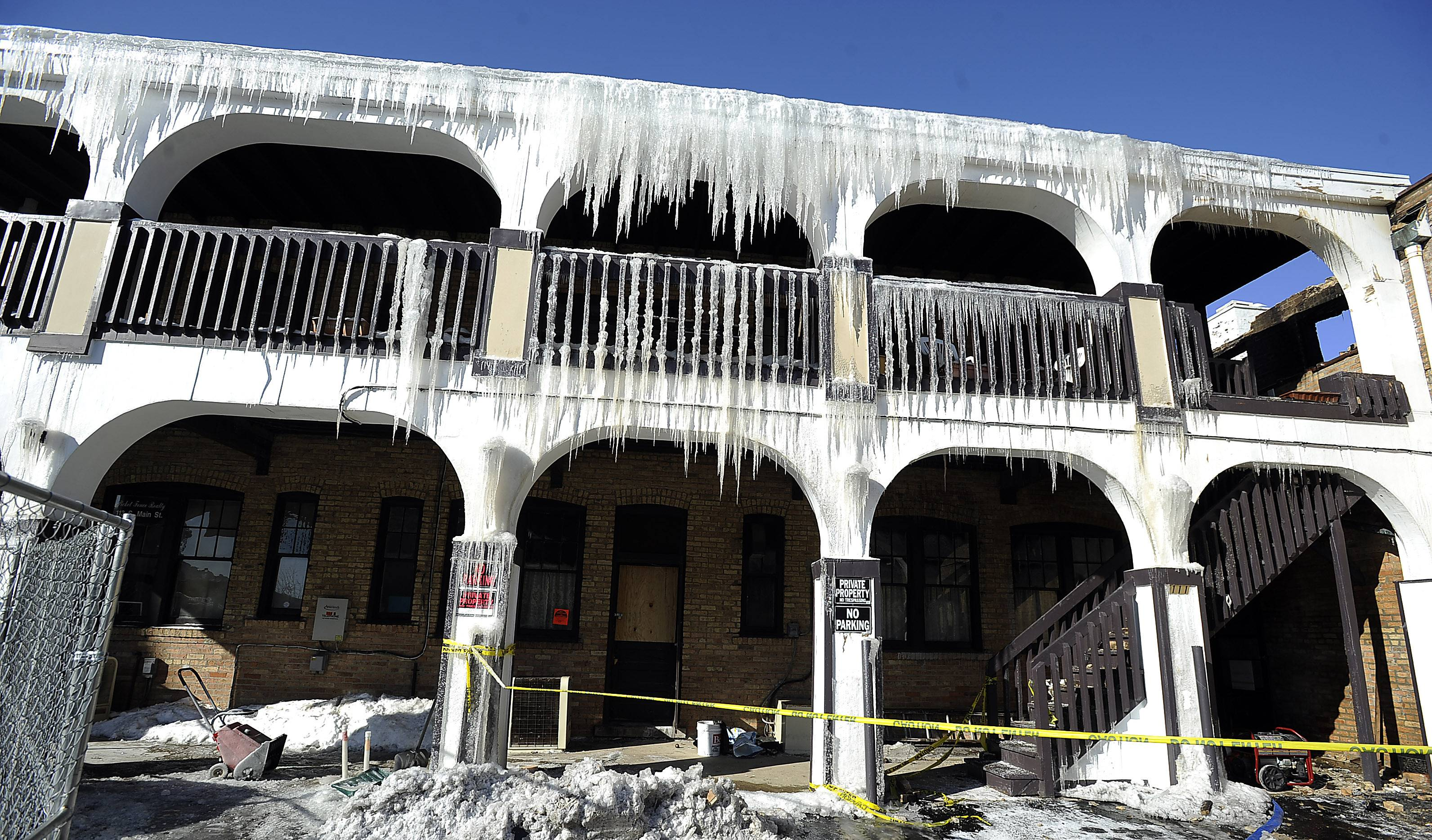 Massive icicles have formed on a 90-year-old building in Mount Prospect where a fire gutted a restaurant, closed other businesses, and left residents homeless.