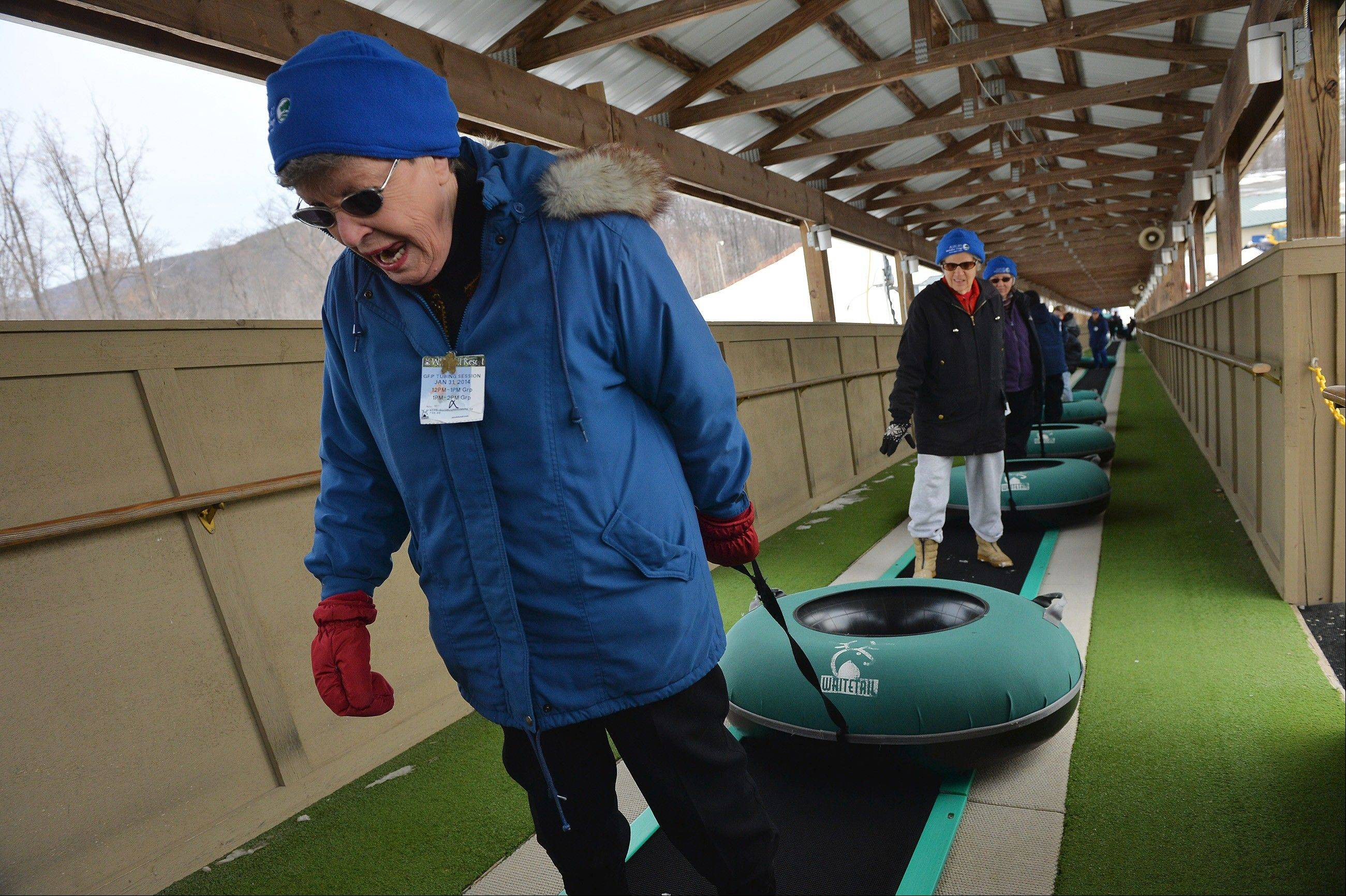 Jan Lafleur, 82, rides a conveyor belt up a hill on Jan. 31, at Whitetail Resort in Mercersburg, Pa. before sliding back down the slope on a snow tube.