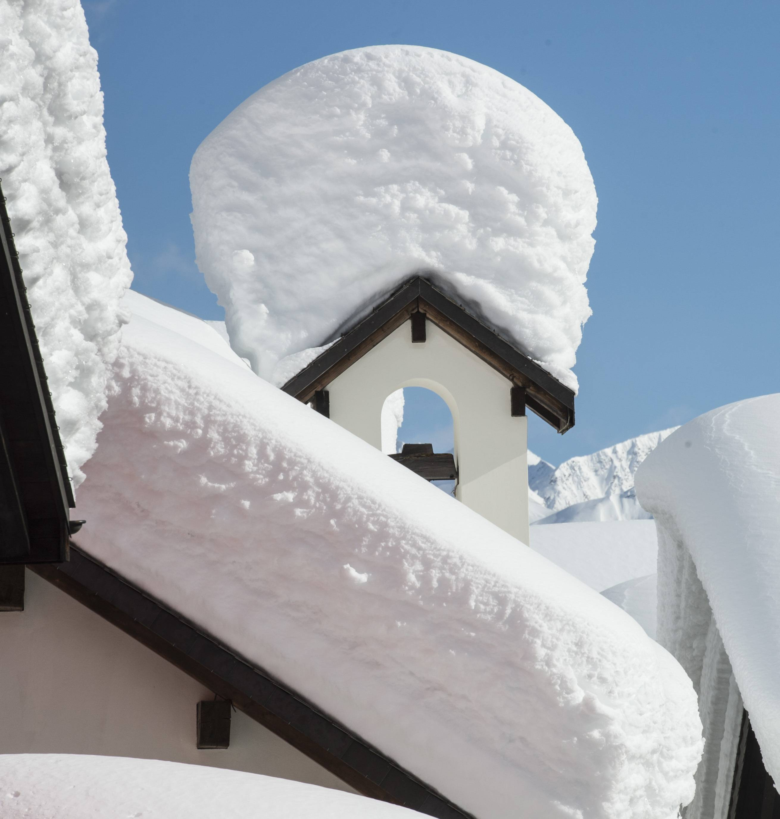 Snow masses pile up on the rooftops in the village of Bedretto, Switzerland, Sunday, Feb. 9, 2014. Weather forecasts predict changeable weather.