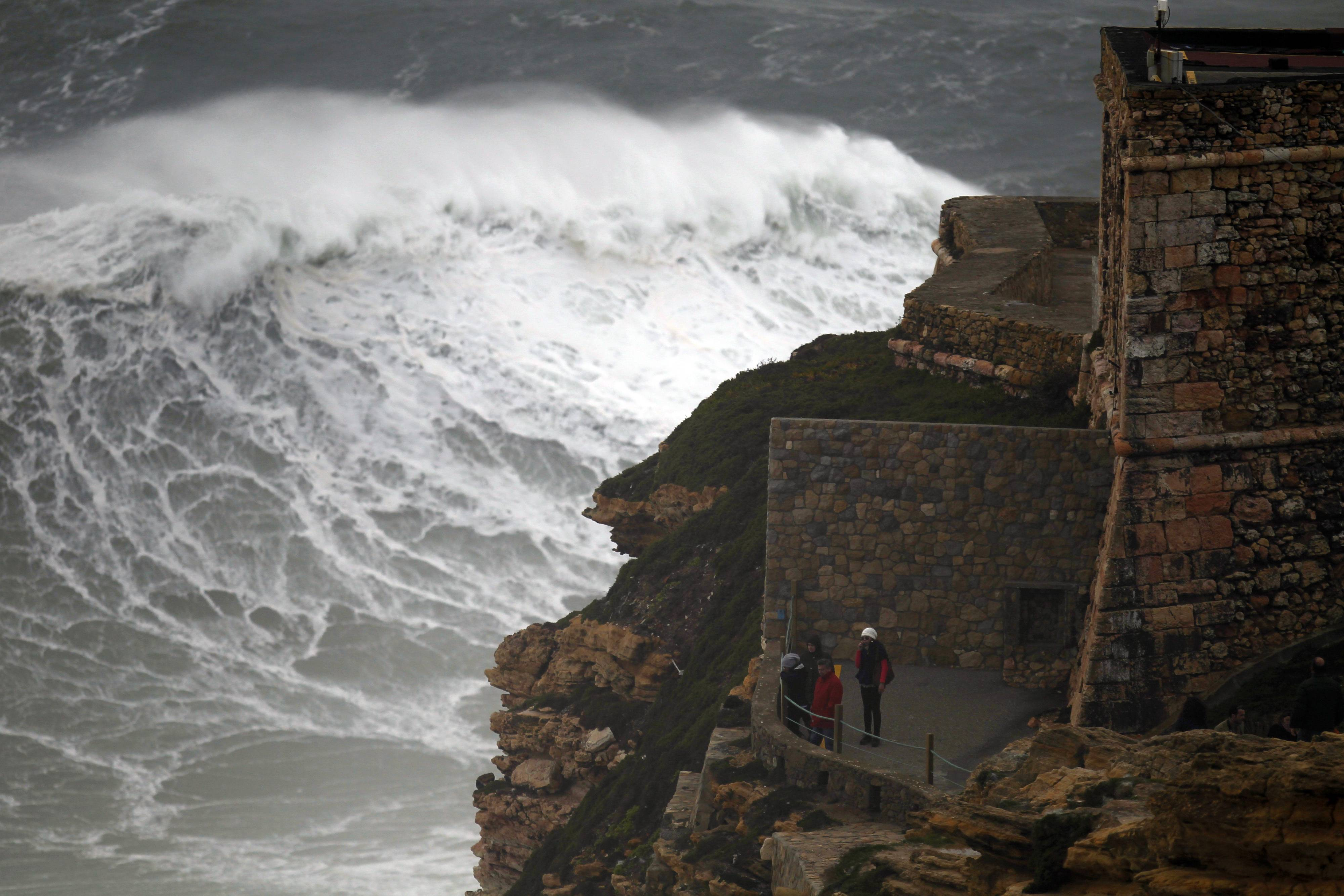 People watch huge waves breaking at the Nazare lighthouse, outside the fishing village of Nazare, on the central coast of Portugal, Saturday, Feb. 8, 2014. The Portuguese weather institute posted a red alert along the central and north coast of Portugal, the highest level of the country's four-alert scale, and few ports were closed due to the rough sea.