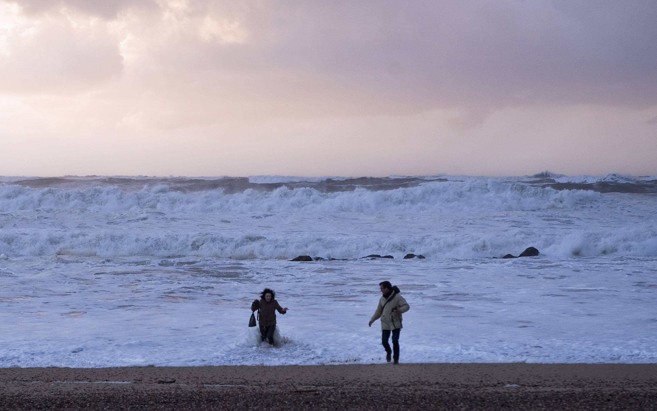 A couple is caught by the sea as rough waves lash the Miramar beach, Vila Nova de Gaia, northern Portugal Saturday, Feb. 8, 2014. The Portuguese weather institute put the entire coast of Portugal on red alert, the most serious in a scale of four, due to rough seas.