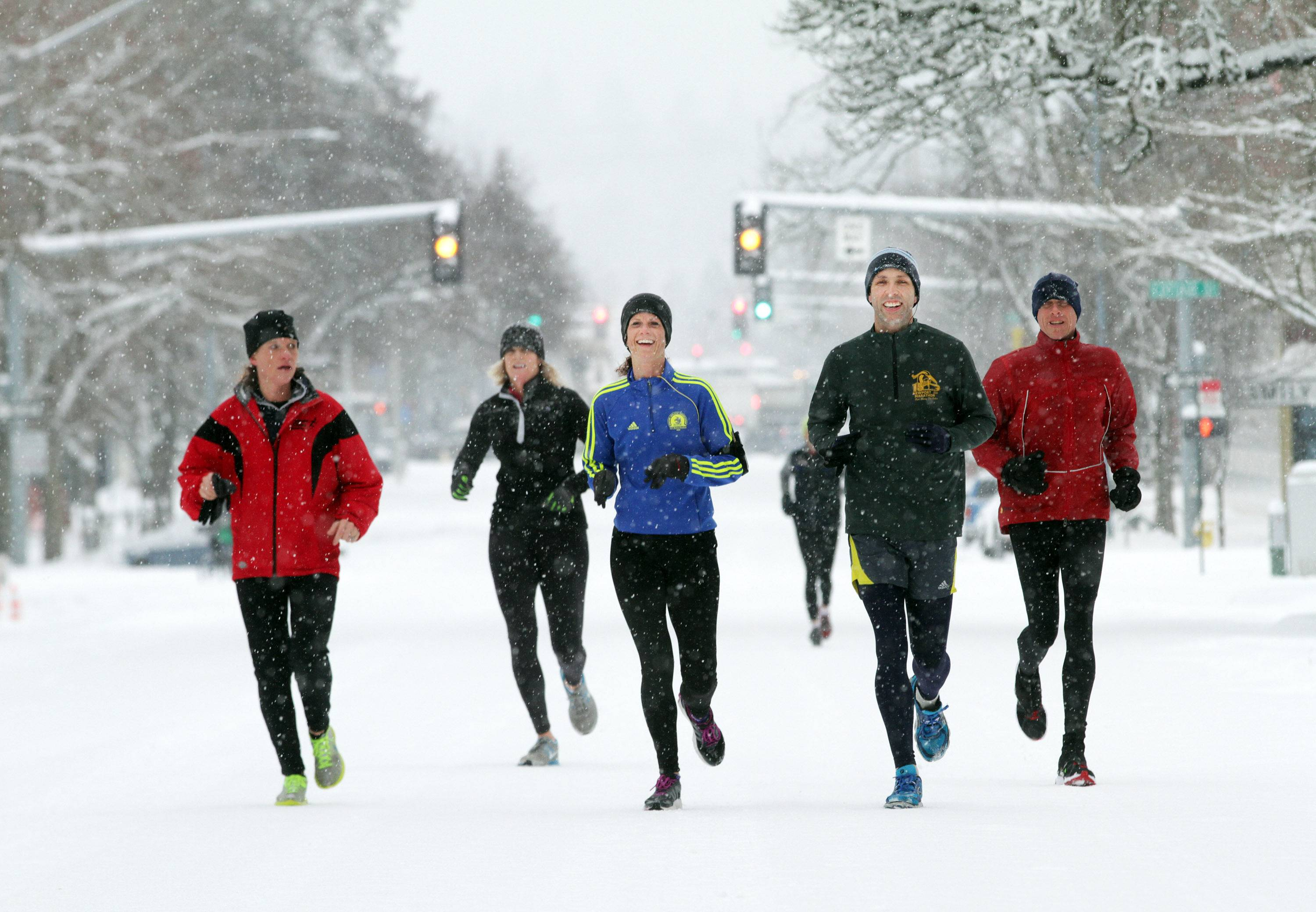 Early morning joggers make their way down the middle of Court St. NE, past the Oregon State Capitol in Salem, Ore. on Saturday, Feb. 8, 2014. Snowfall begins again in earnest for the third day, as Salem remains largely shut down due to a winter storm.