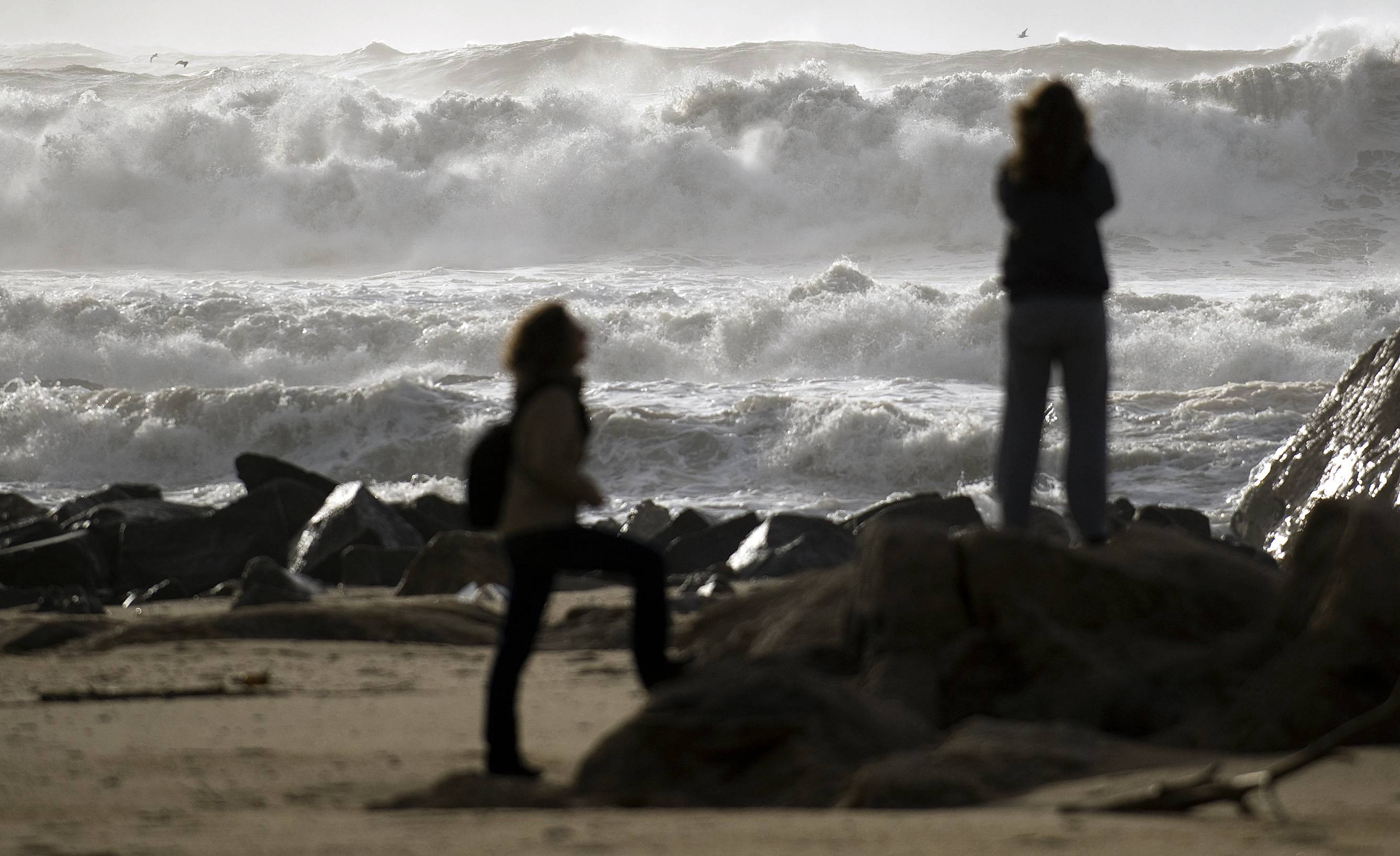 Women take photographs as rough waves lash the Miramar beach, Vila Nova de Gaia, northern Portugal Saturday, Feb. 8, 2014. The Portuguese weather institute put the entire coast of Portugal on red alert, the most serious in a scale of four, due to rough seas.