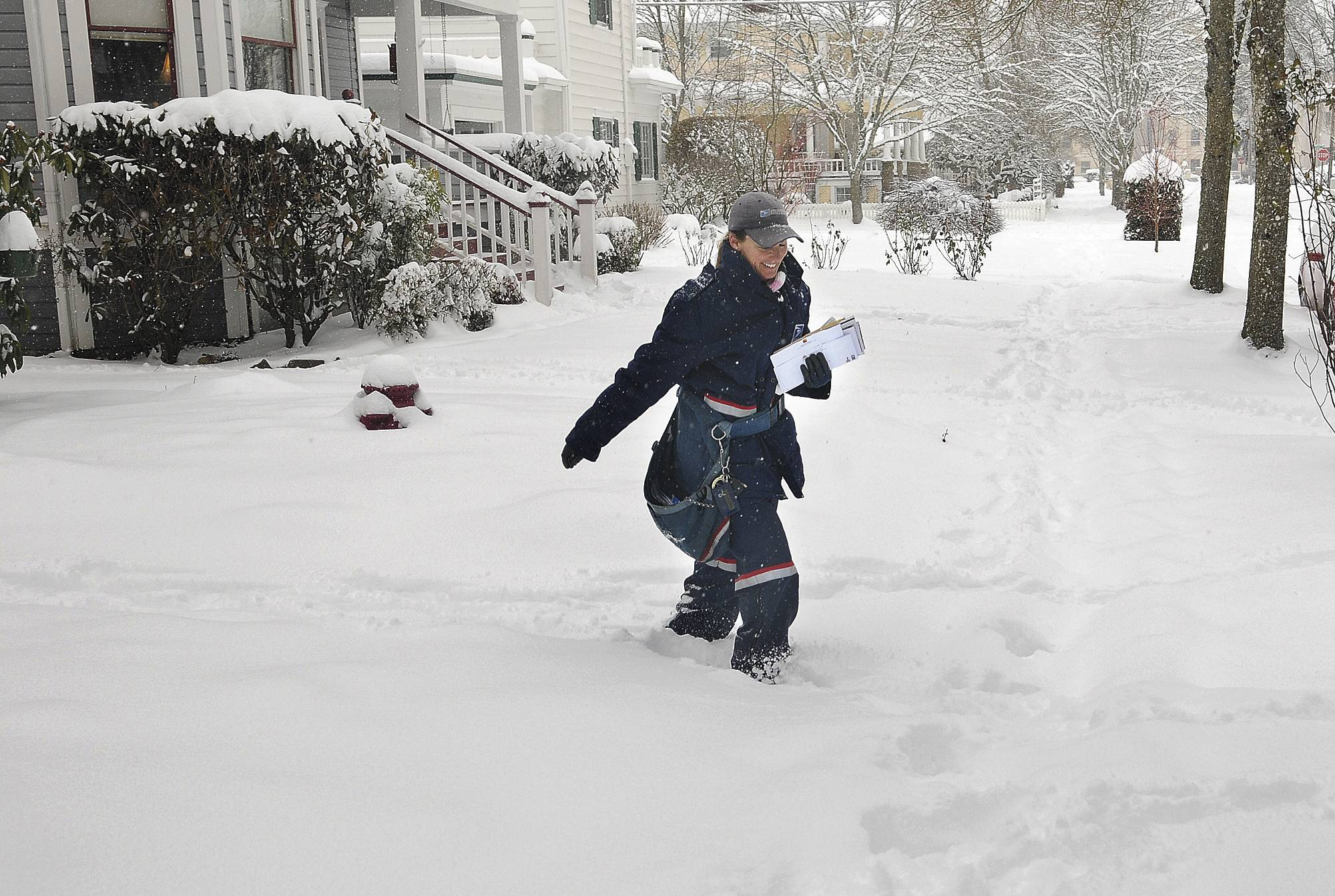 Mail carrier Tammie Harris trudges through the snow while delivering to homes in the Monteith District of Albany, Ore., Friday, Feb. 7, 2014. More than a foot of snow has fallen in the Willamette Valley community during the last two days. The area, known for its rain, rarely sees more than a few inches of the white stuff a year.