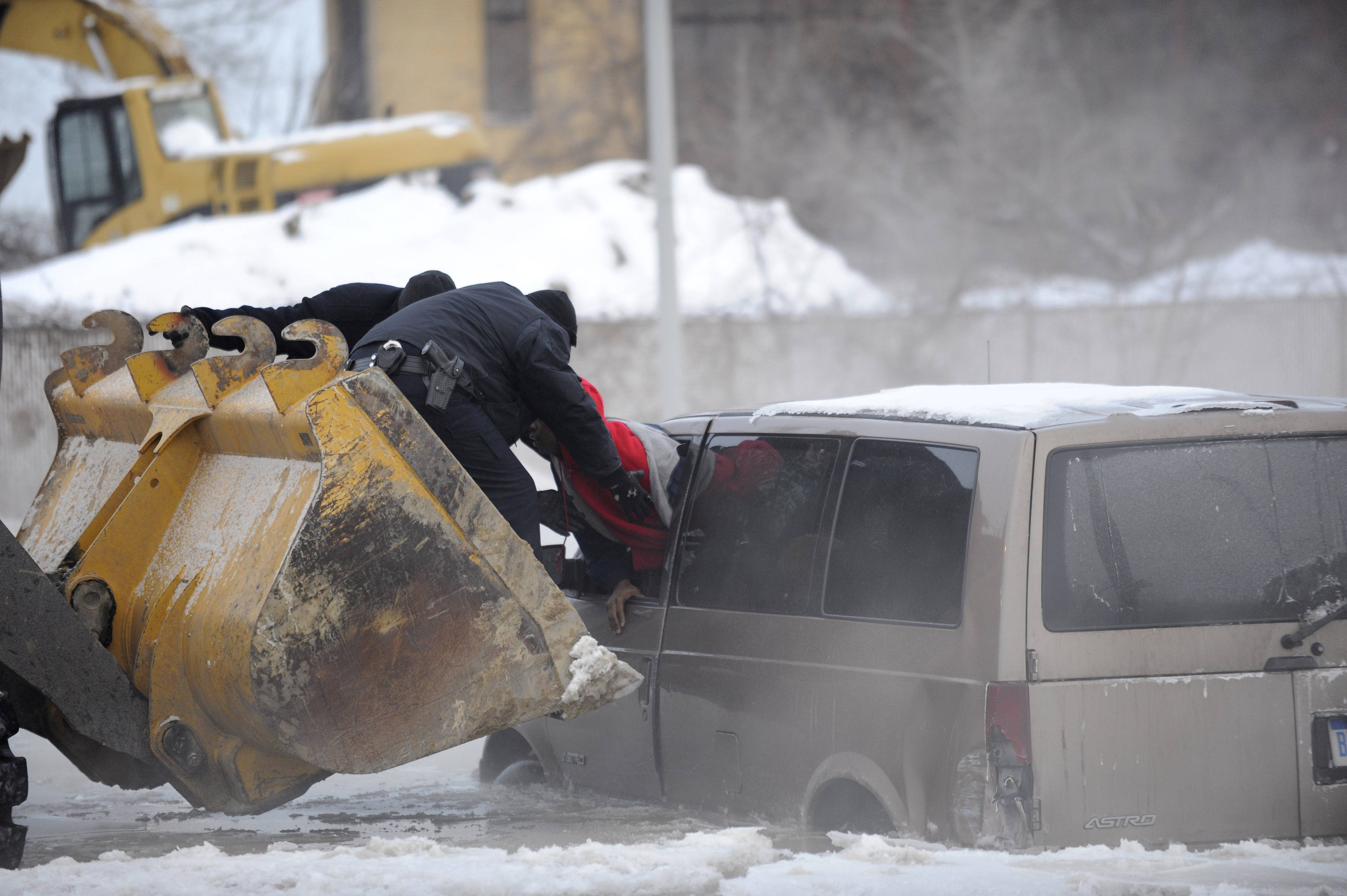 Detroit police use the scoop of a front-end loader to carry two people stranded in a minivan to safety after street flooding caused by a water main break on Friday, Feb. 7, 2014 on Detroit's east side. Several vehicles were stuck in water and ice, prompting a rescue by police officers on construction equipment. The break was reported about 5 a.m. Friday in the area of Gratiot Avenue at Conner Street. The scoop of a front-end loader was used to carry two people stranded in a minivan. Crews also worked to clear ice and water from the area, which is closed to traffic. No injuries were reported.