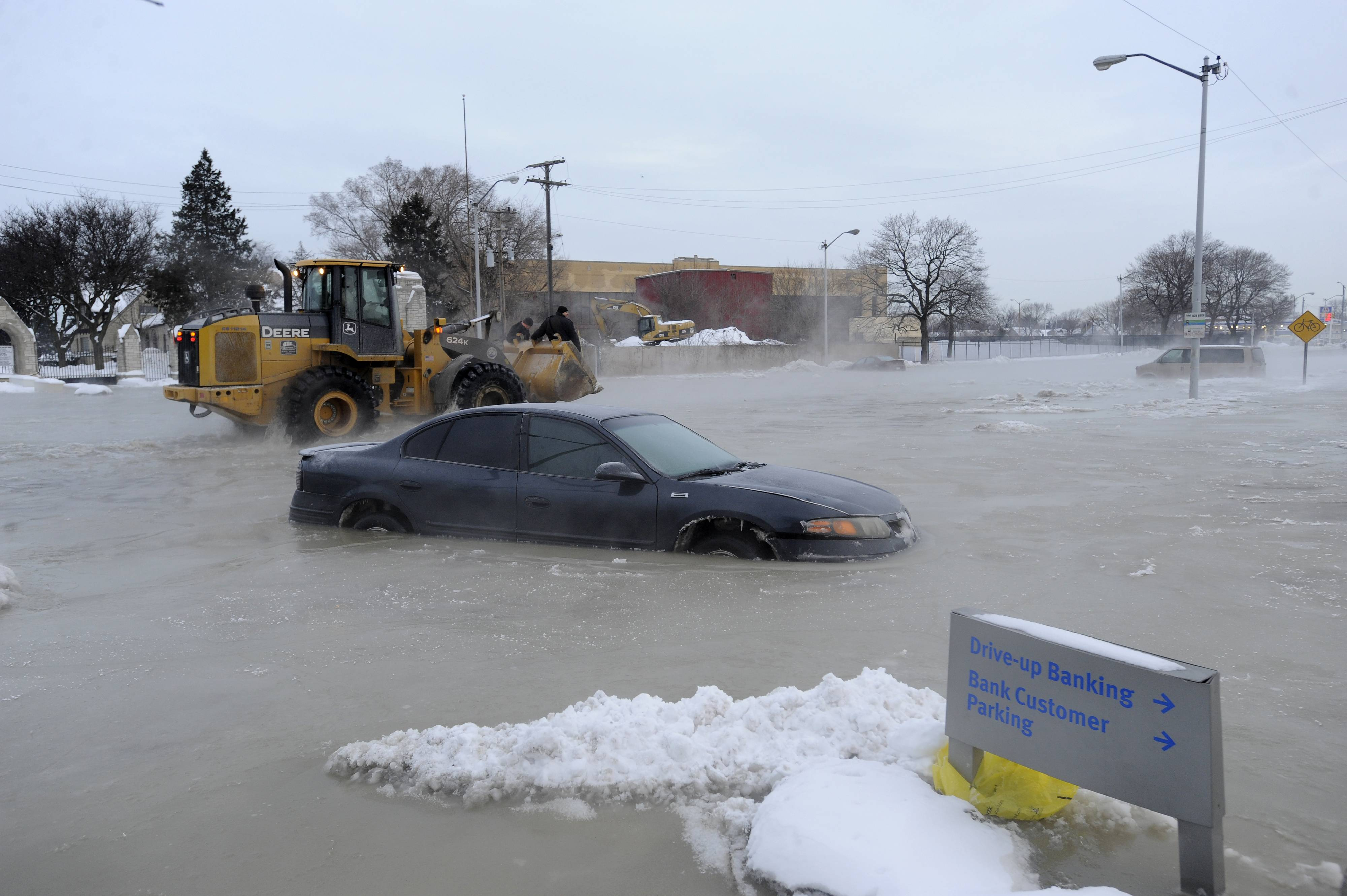 Street flooding caused by a water main break on Friday, Feb. 7, 2014 on Detroit's east side left several vehicles stuck in water and ice, prompting a rescue by police officers on construction equipment. The break was reported about 5 a.m. Friday in the area of Gratiot Avenue at Conner Street. Police and firefighters responded to help free motorists. The scoop of a front-end loader was used to carry two people stranded in a minivan. Crews also worked to clear ice and water from the area, which is closed to traffic. No injuries were reported.