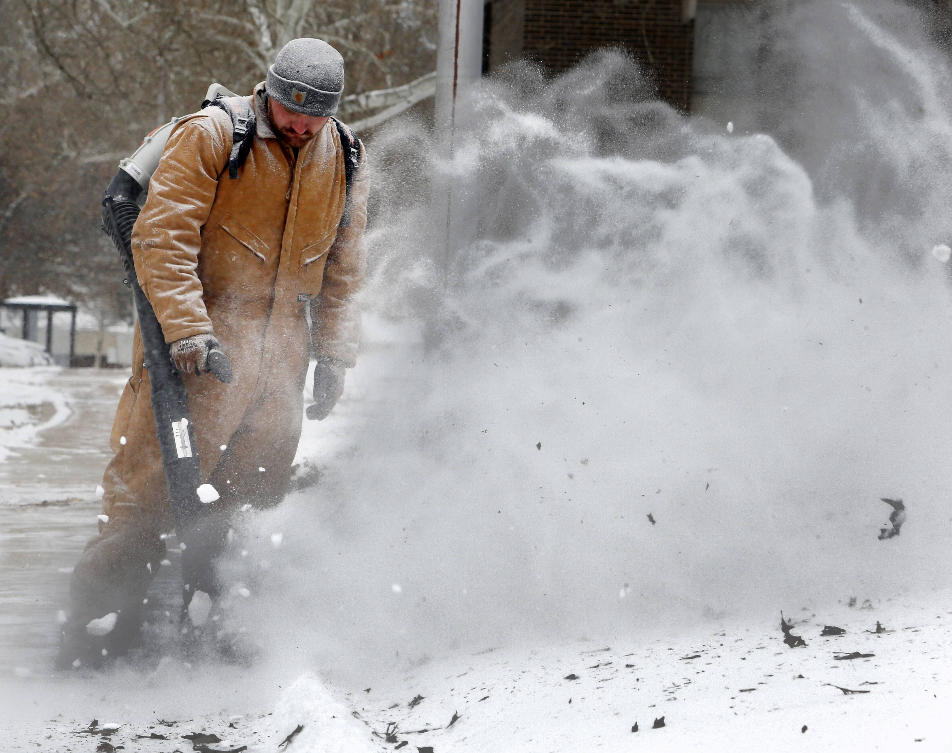 Eric Davis, irrigation department, uses a backpack blower to remove snow from sidewalks in frigid weather on the campus of the University of Oklahoma on Thursday, Feb. 6, 2014, in Norman, Okla.