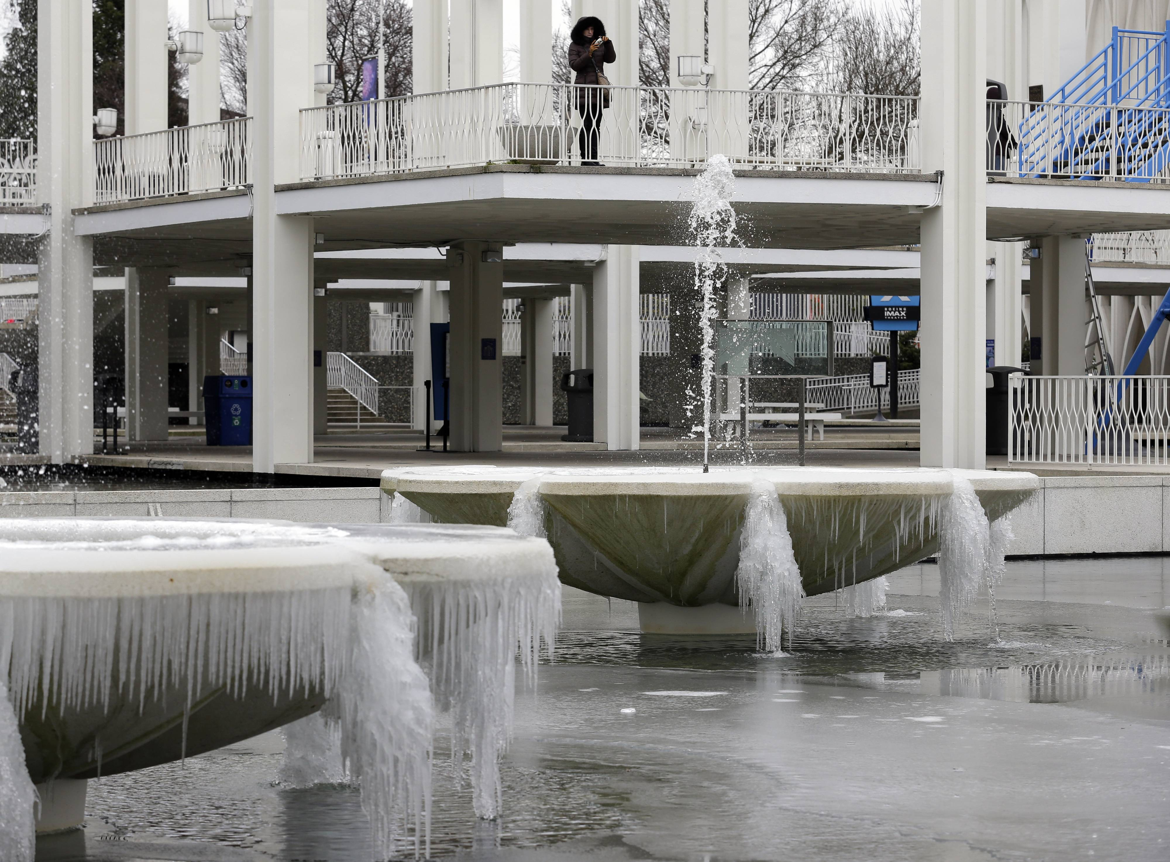 A visitor photographs frozen fountains caked with ice at the Pacific Science Center in Seattle, Thursday, Feb. 6, 2014. Below-normal, frigid temperatures are forecast to continue into the weekend in Washington and then begin to moderate next week.