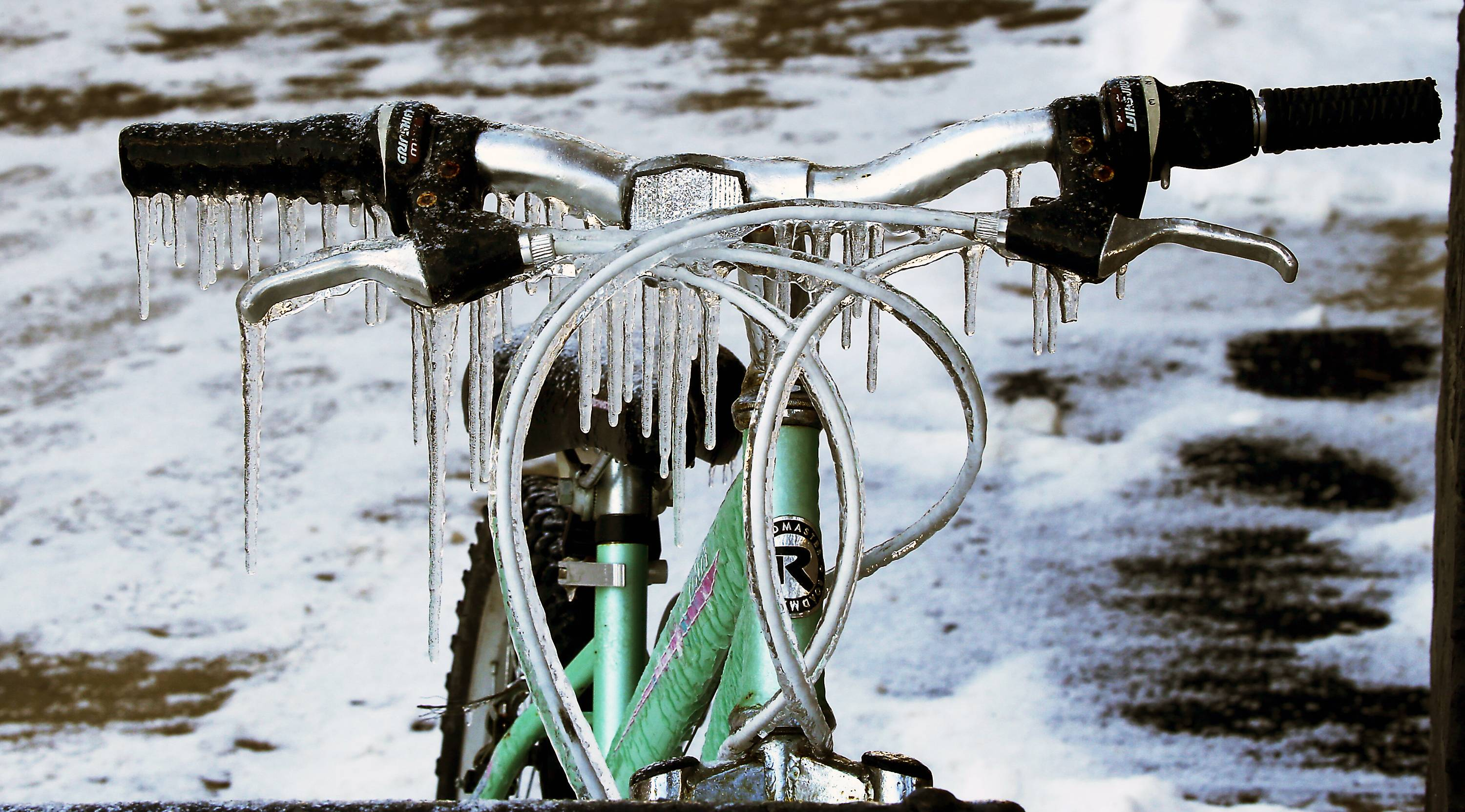 Icicles hang from the handlebars of a bicycle outside a coffee shop in Harmony, Pa., Thursday, Feb. 6, 2014.