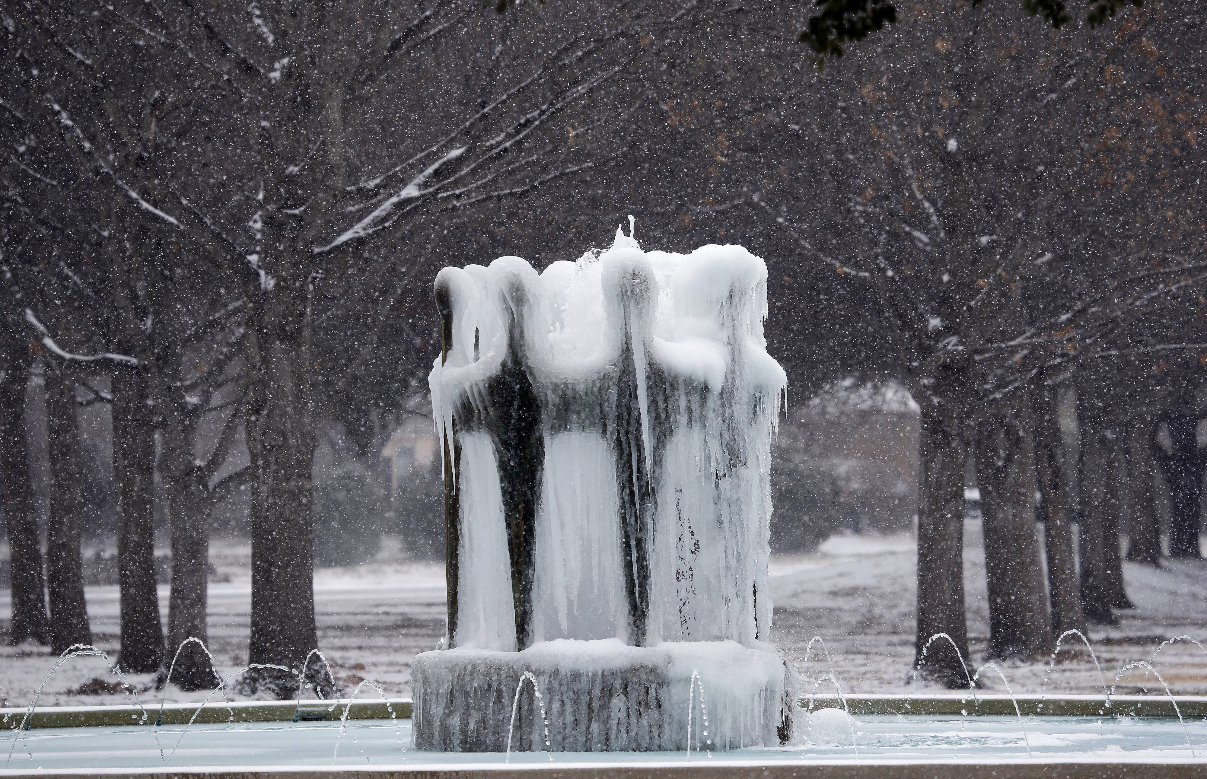 Ice forms on a water fountain as a light snow falls in Richardson, Texas, Thursday, Feb. 6, 2014. The National Weather Service recorded light snow Thursday in Austin, Dallas-Fort Worth, Abilene, Midland-Odessa, San Angelo and Lubbock.