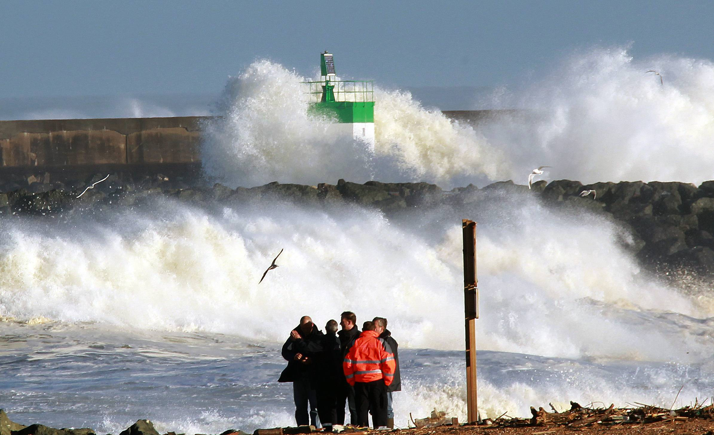 People look big waves of Atlantic Ocean in Anglet, southwestern France, Thursday, Feb. 6, 2014. There is a weather alert for high waves in the south west of France, lasting until Saturday.