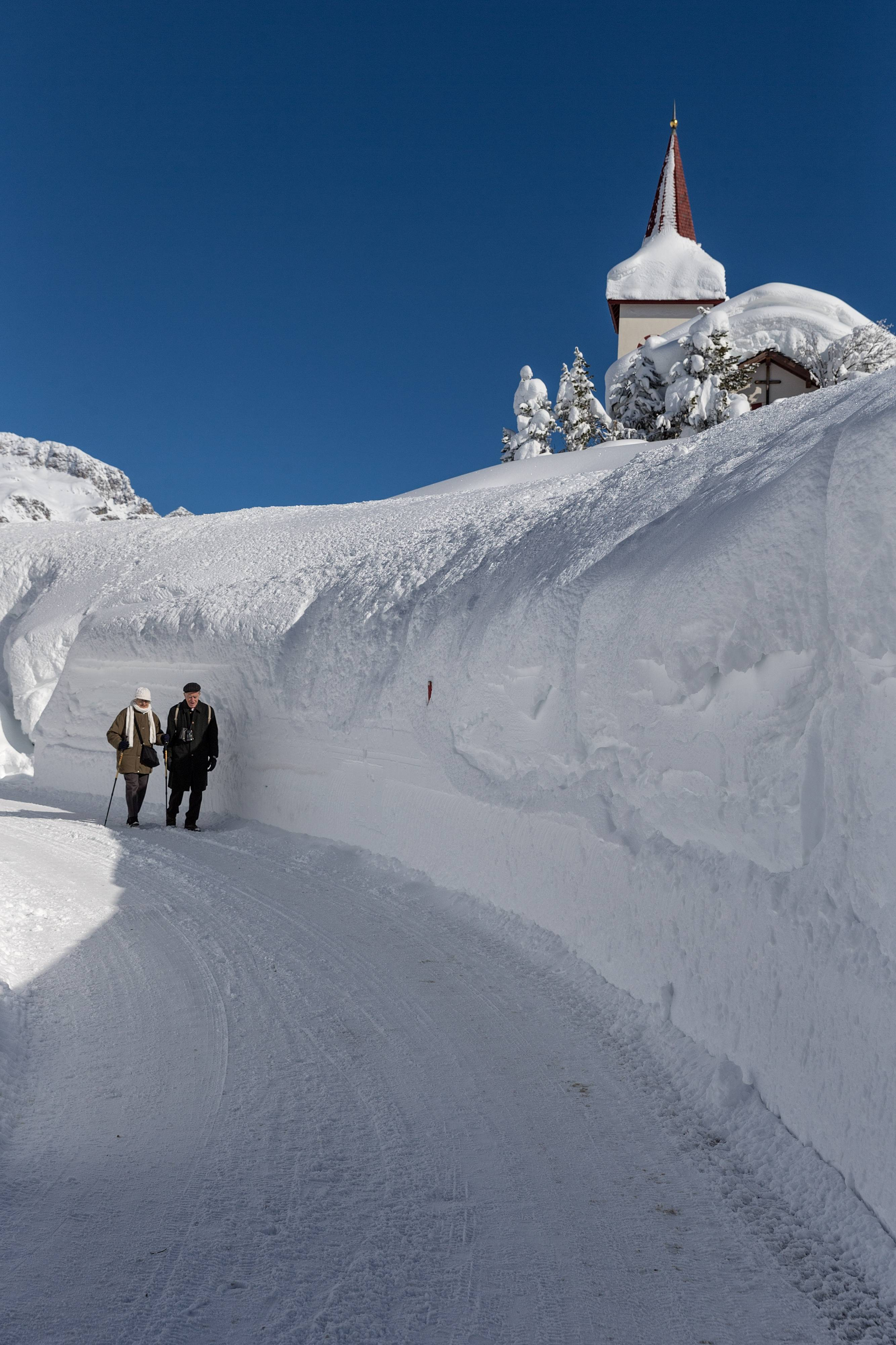 Hikers walk in a snowy street in Maloja, Switzerland Thursday Feb. 6, 2014. Weather forecasts predict changeable weather.