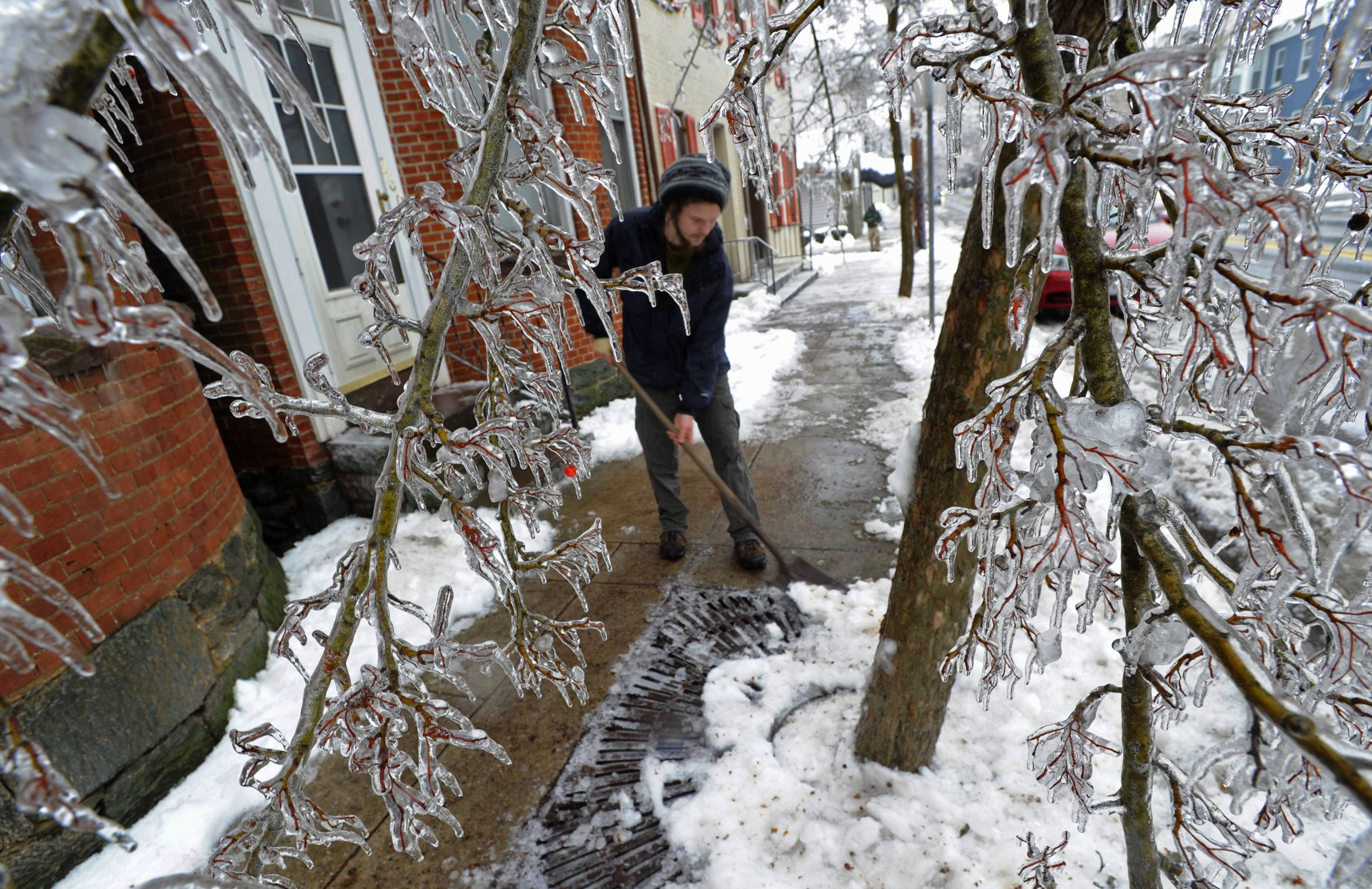 Adam Caprarola clears ice from a sidewalk along East Main Street after a winter storm with freezing rain downed trees and left thousands without electricity, Wednesday, Feb 5, 2014, in Westminster, Md.
