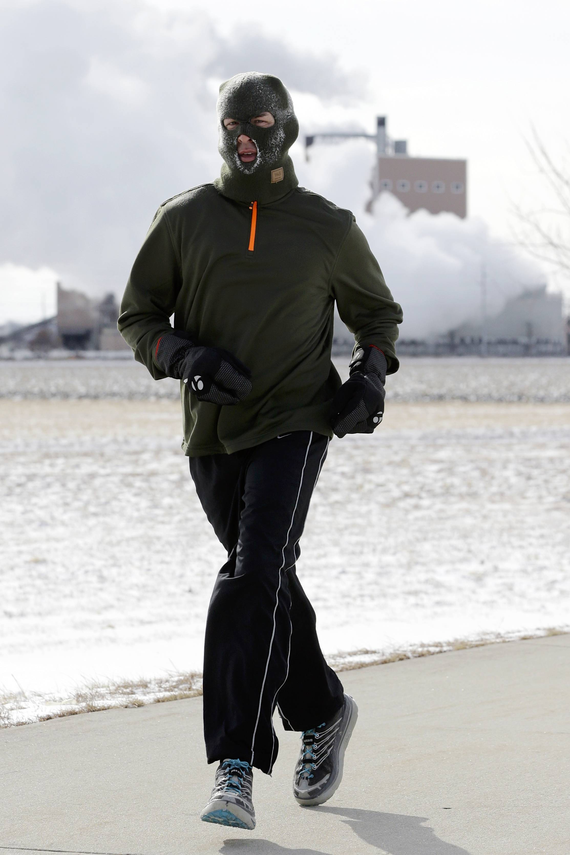 A man jogs in freezing temperatures on a path in Fremont, Neb., Thursday, Feb. 6, 2014.