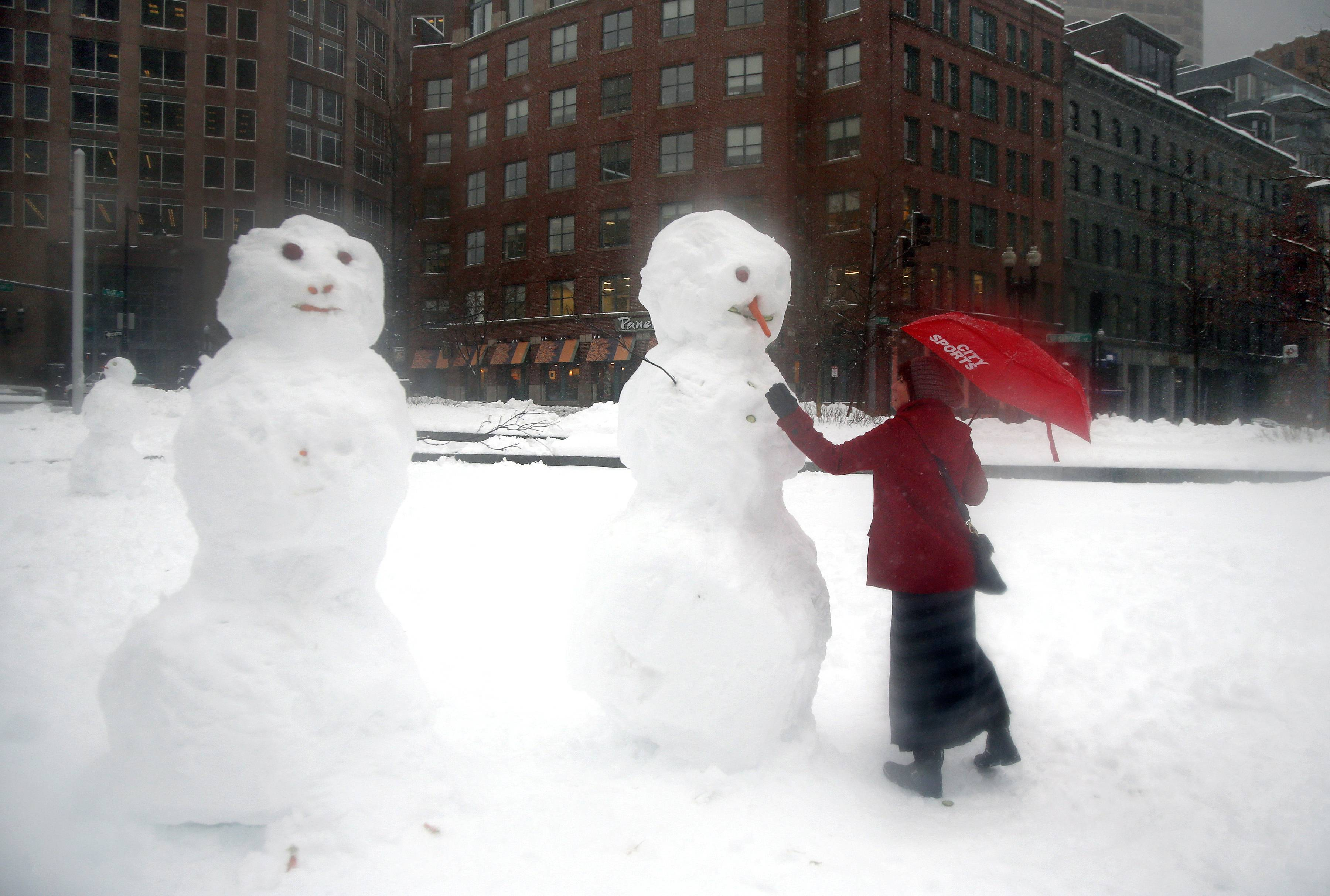 Shawn Meisl puts a finishing touch on a snowman in downtown Boston, Wednesday, Feb. 5, 2014. Up to a foot of snow was predicted to fall in parts of Massachusetts.