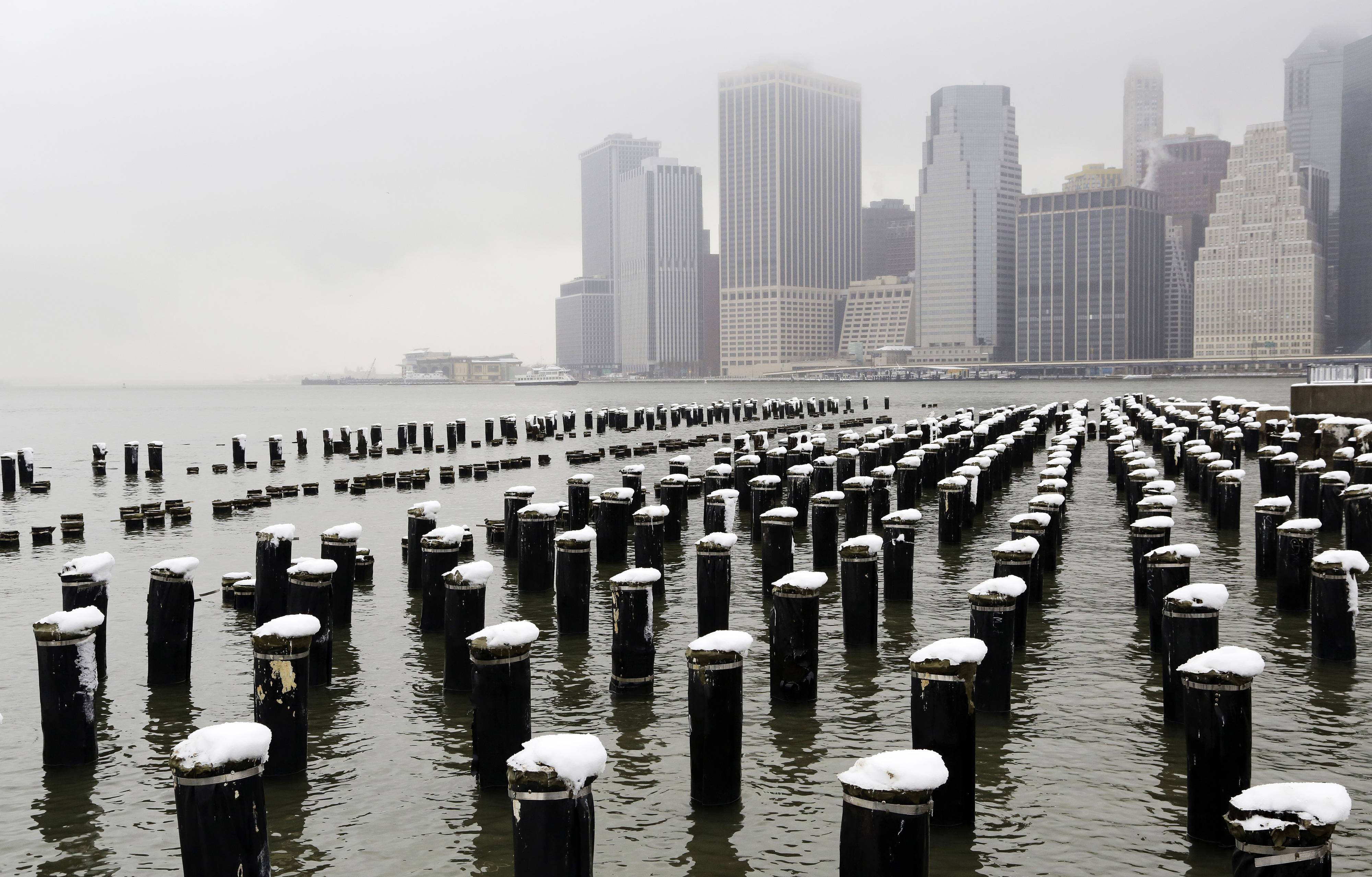 Snow-capped pilings dot the Brooklyn waterfront with the Manhattan skyline in the background Wednesday, Feb. 5, 2014, in New York. Gov. Andrew Cuomo declared a statewide state of emergency, closing Interstate 84 between the Connecticut and Pennsylvania borders until midafternoon.
