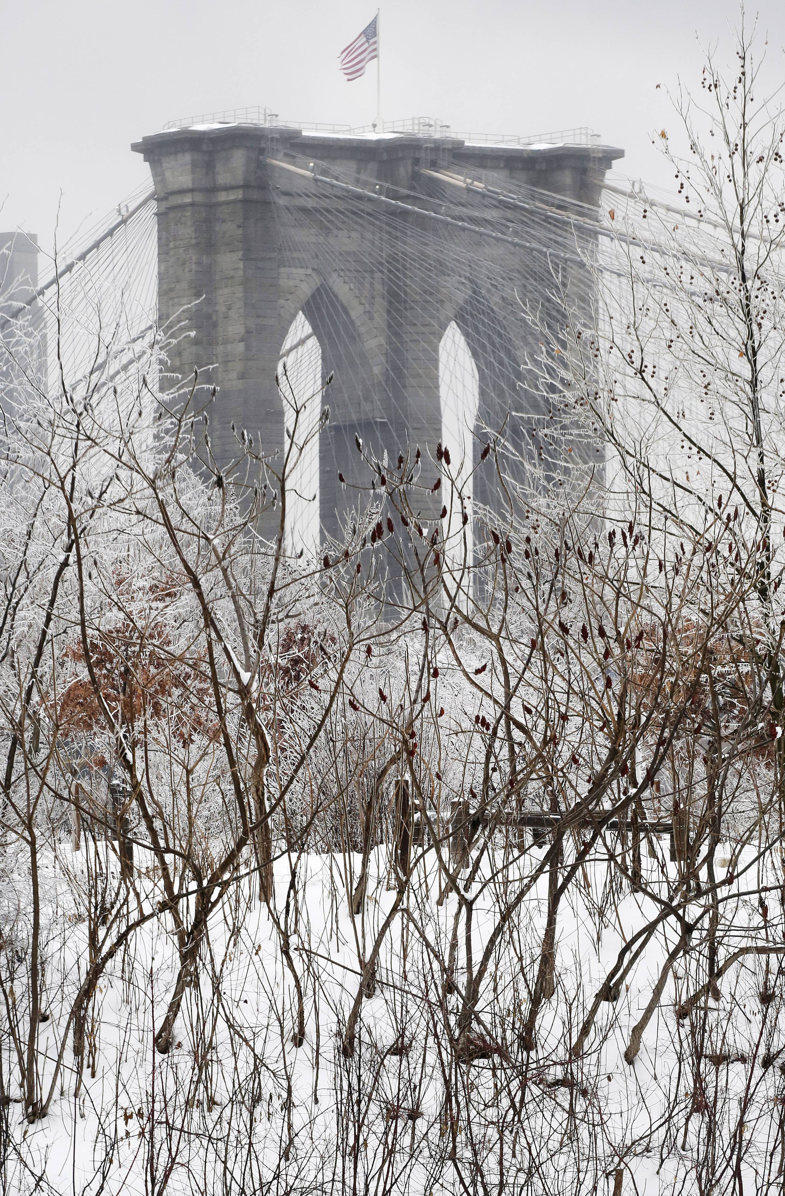 The Brooklyn Bridge overlooks a snow-covered park Wednesday, Feb. 5, 2014, in New York. Gov. Andrew Cuomo declared a statewide state of emergency, closing Interstate 84 between the Connecticut and Pennsylvania borders until midafternoon.