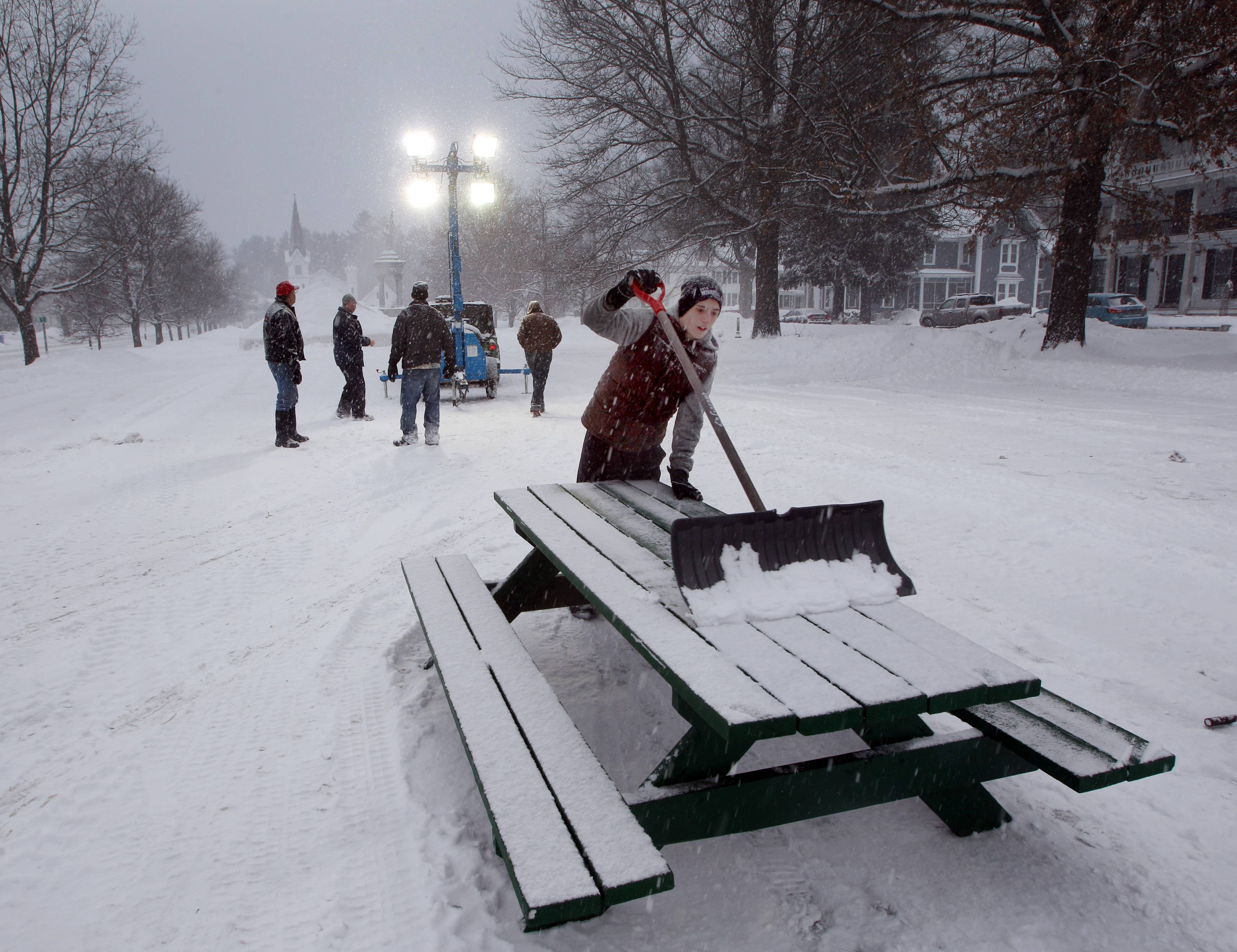 "Dylan Palmer works to keep tables clear of snow before the ""Yankee Luau"" on the town common as part of the towns 98th Winter Carnival Wednesday Feb. 5, 2014 in Newport, N.H."