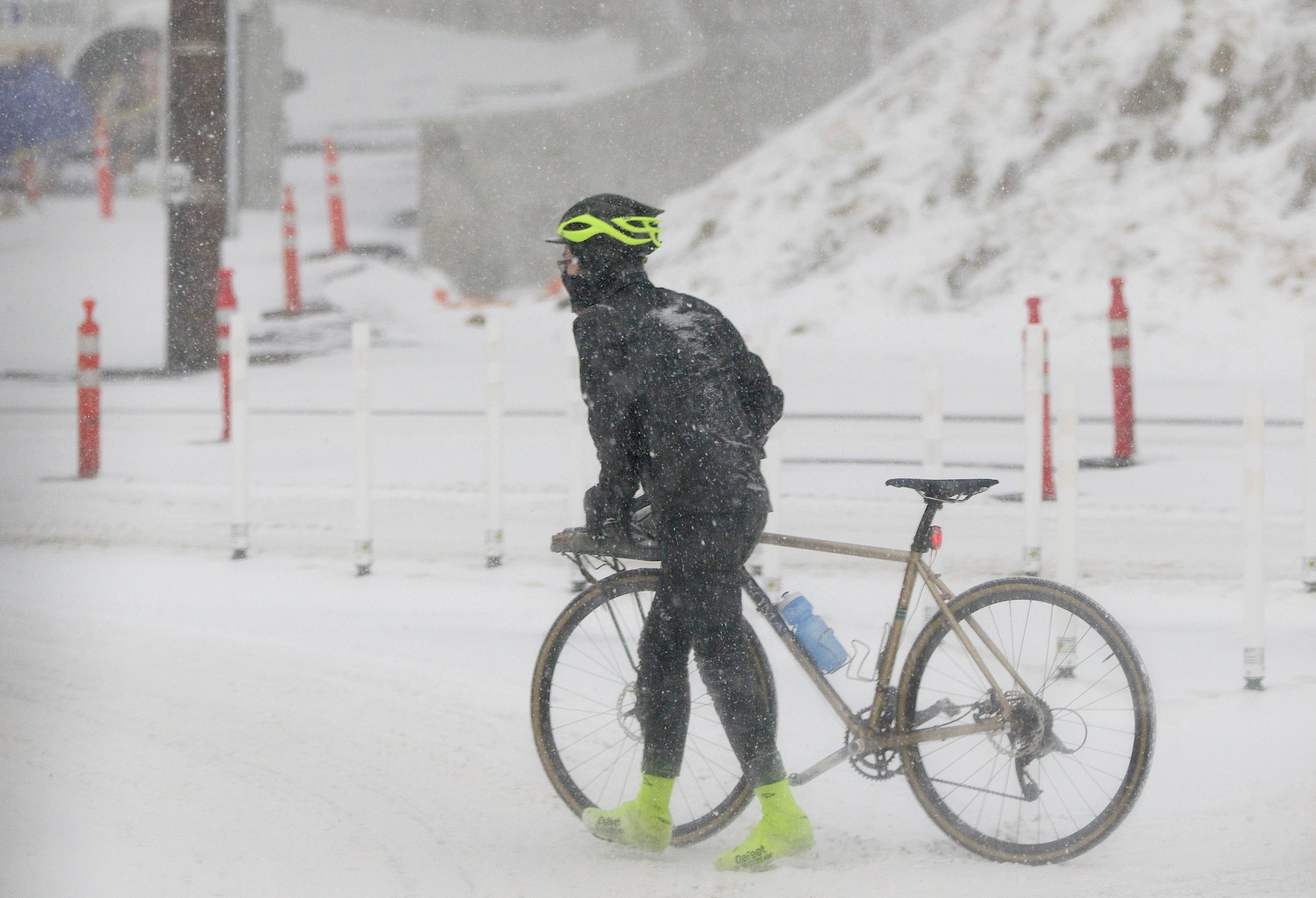 In this photo taken on Thursday, Feb. 6, 2014, s cyclist uses the pedestrian crossing at the west end of the Sellwood Bridge at Highway 43 during a snowstorm in Portland, Ore.