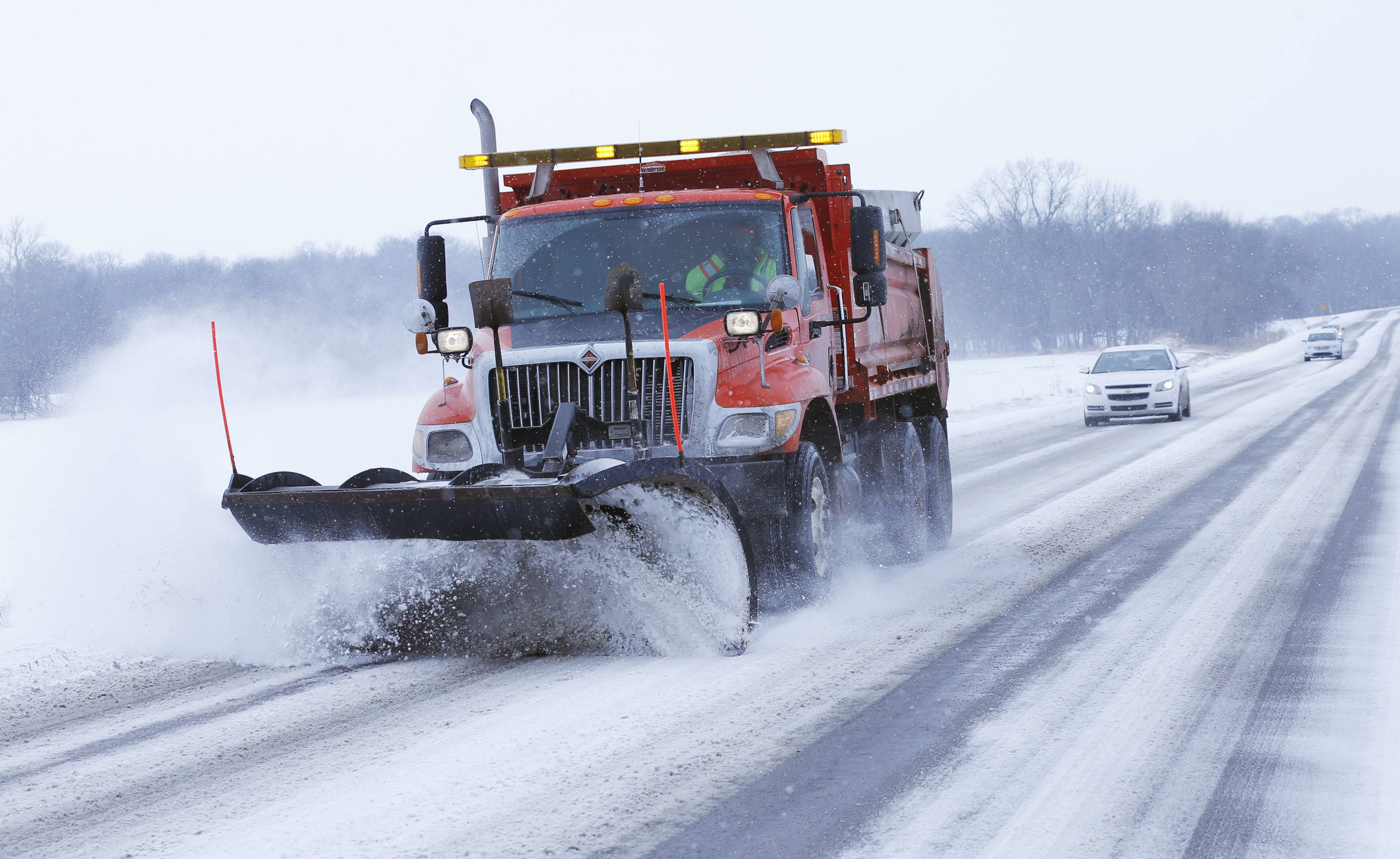 A plow removes snow from US24 near Reno, Kan., Sunday, Feb. 9, 2014.