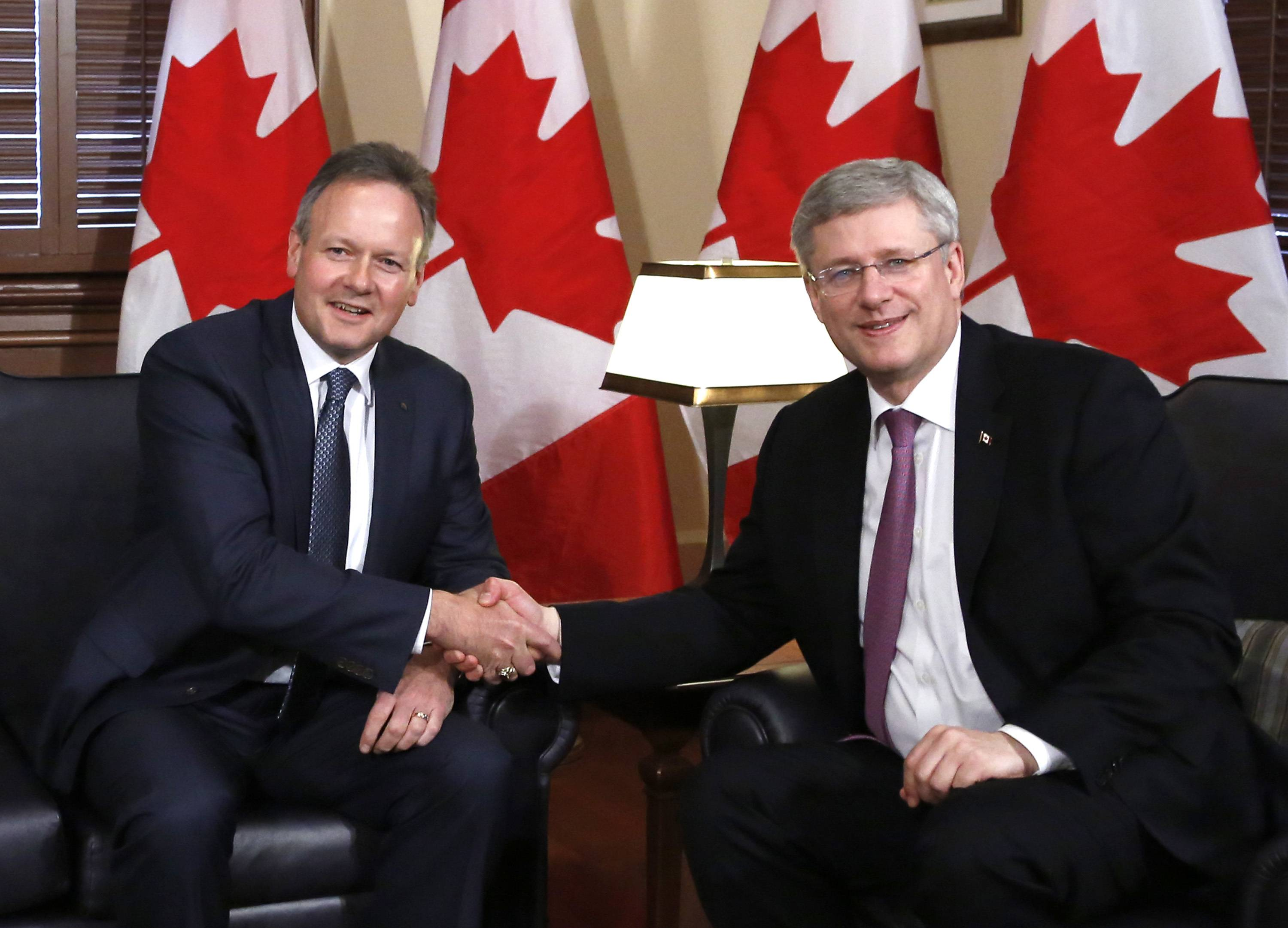 Stephen Poloz, governor of the Bank of Canada, left, shakes hands with by Stephen Harper, Canada's prime minister, right, while being welcomed into office in Ottawa, Ontario, Canada.