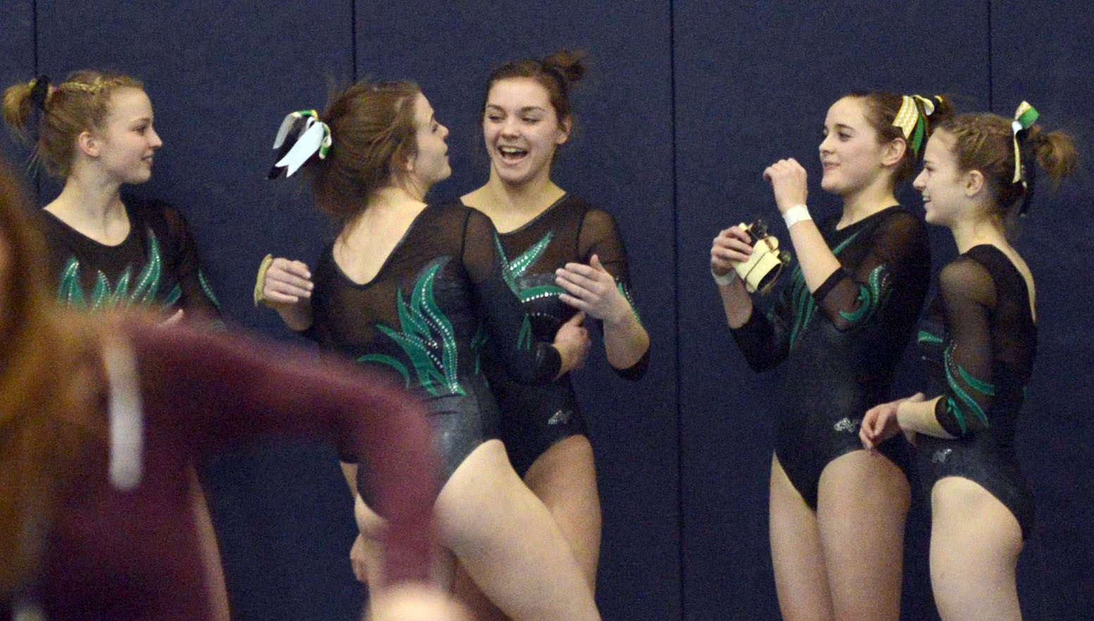 Fremd gymnasts congratulate one another after their performances on floor exercise during the Conant sectional Monday night.