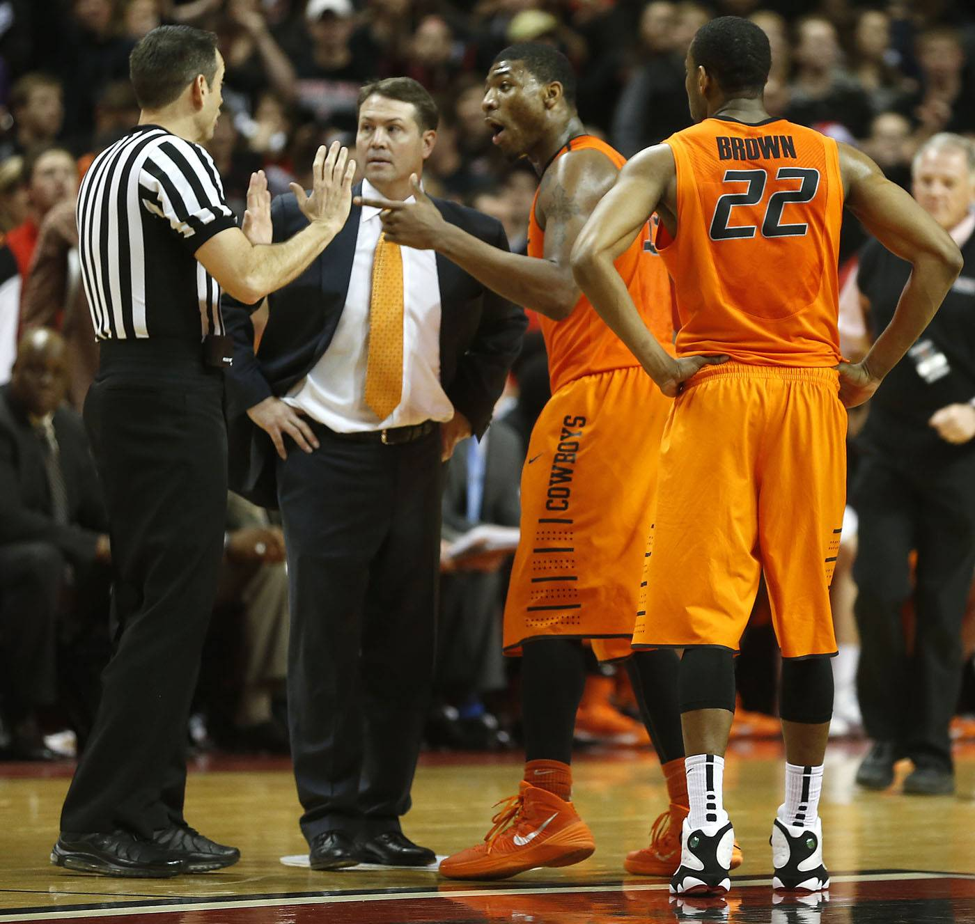Associated PressOklahoma State head coach Travis Ford, center, Marcus Smart and Markel Brown(22) speak to the referee after Smart shoved a fan Saturday during a NCAA college basketball game in Lubbock, Texas.