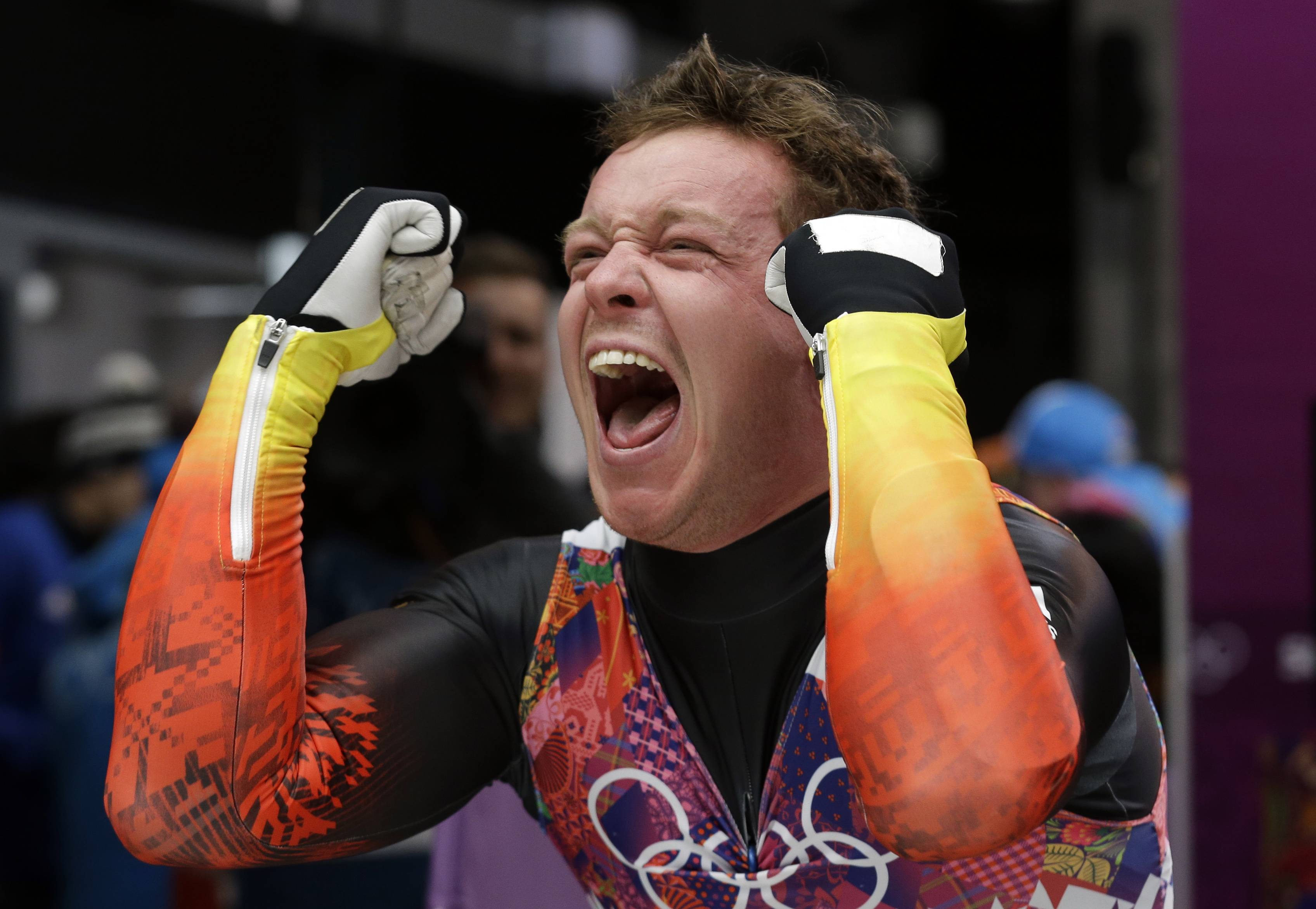 Felix Loch of Germany celebrates after he crossed the finish area to win the gold medal during the men's singles luge final .