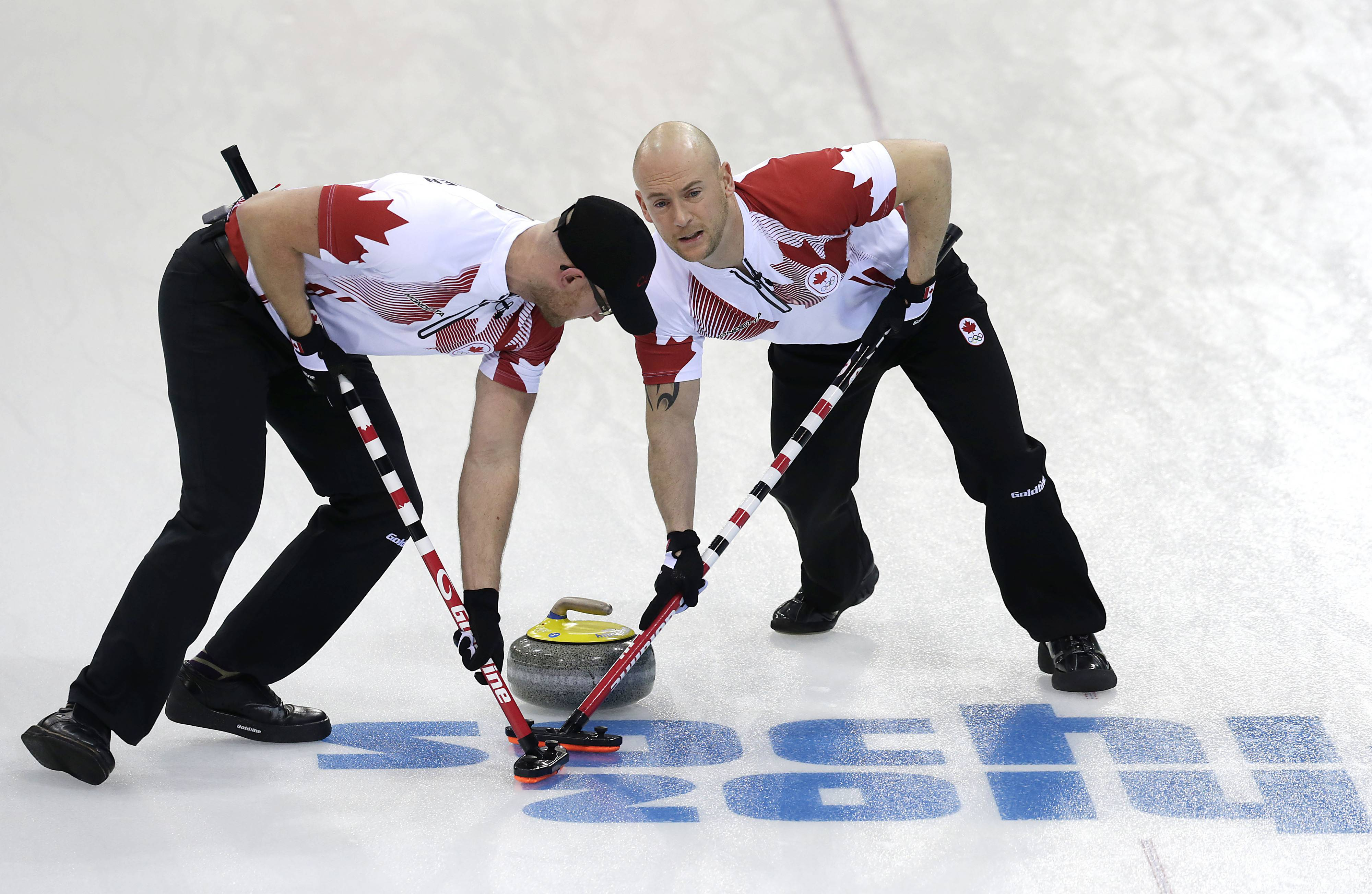 Canada's Ryan Fry, right, and Ryan Harnden, left, sweep the ice during the men's curling competition against Germany.