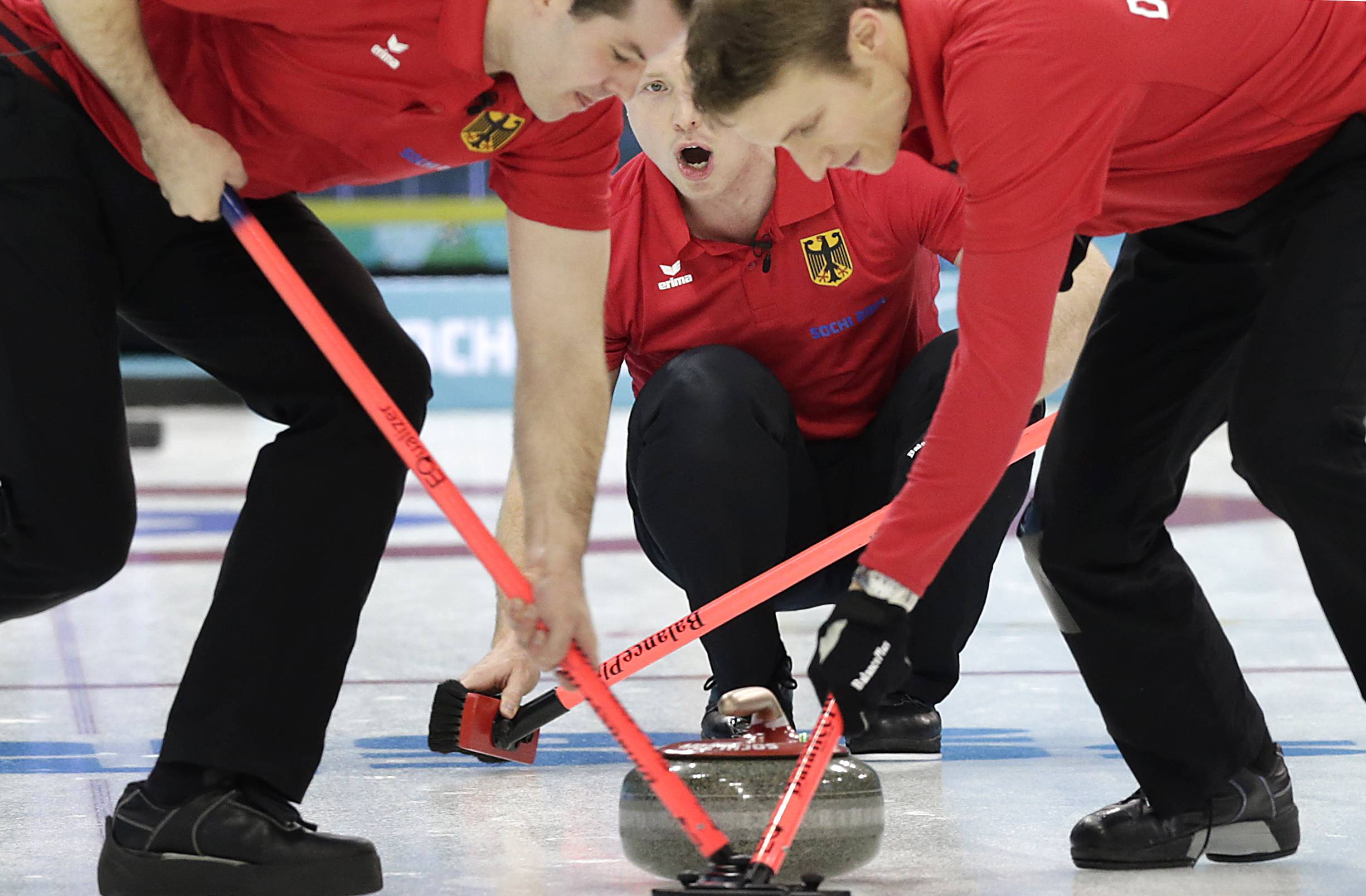 Germany's Christopher Bartsch, center, shouts instructions to his sweepers Felix Schulze, left, and Peter Rickmers, right, during the men's curling competition against Canada.