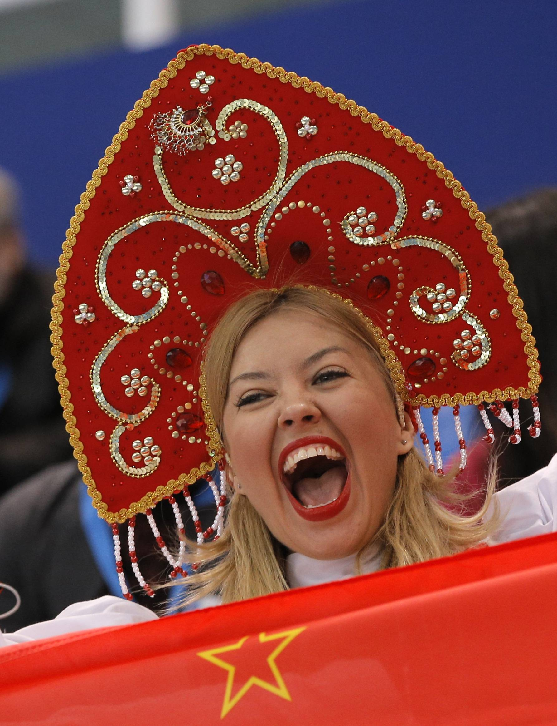 A spectator cheers as she stands behind a flag of the Soviet Union before the short track speed skating competition.