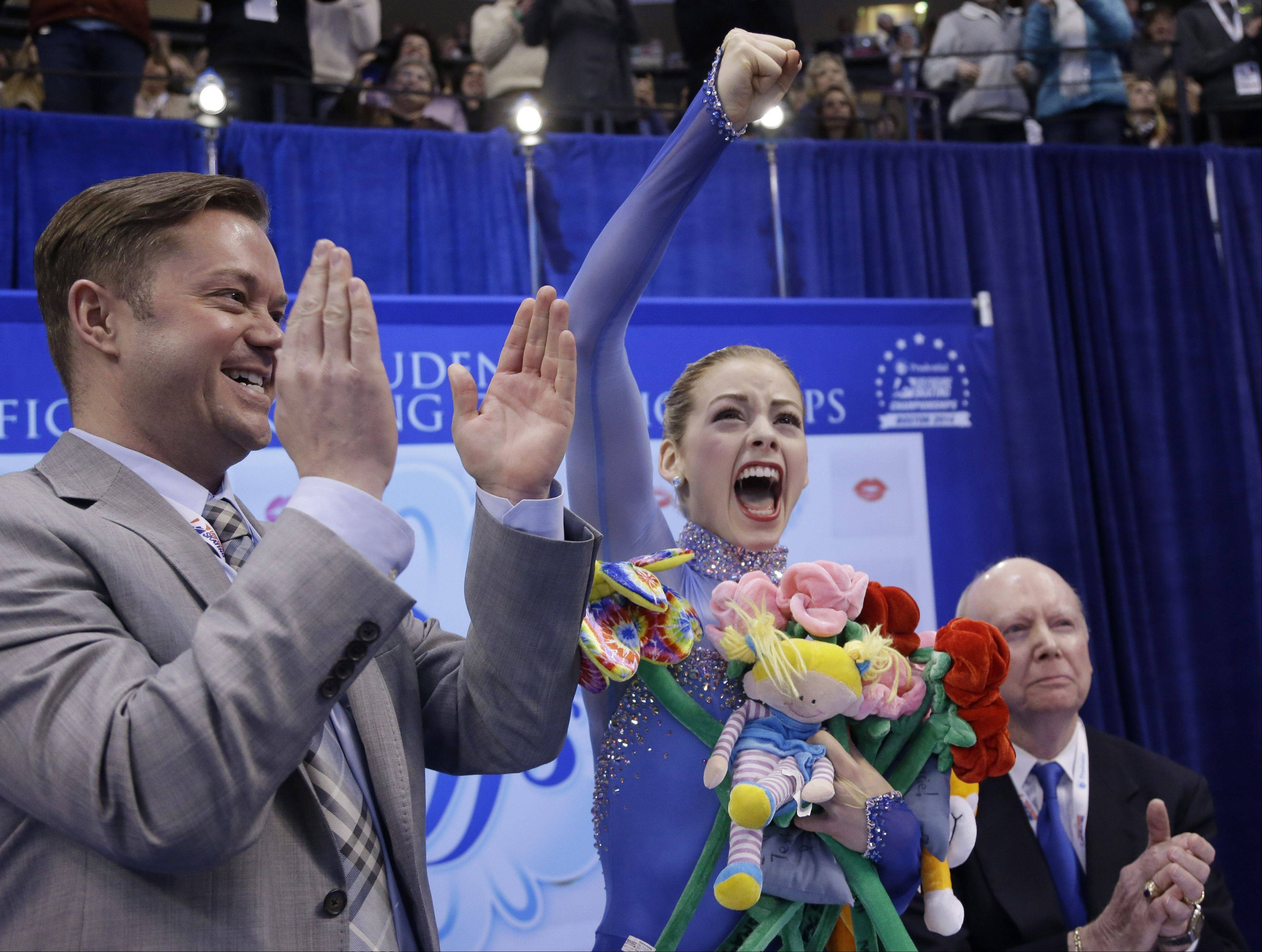 Gracie Gold, center, celebrates as she learns her scores for the women's free skate as her coaches Scott Brown, left, and Frank Carroll, right, applaud at the U.S. Figure Skating Championships Jan. 11 in Boston.