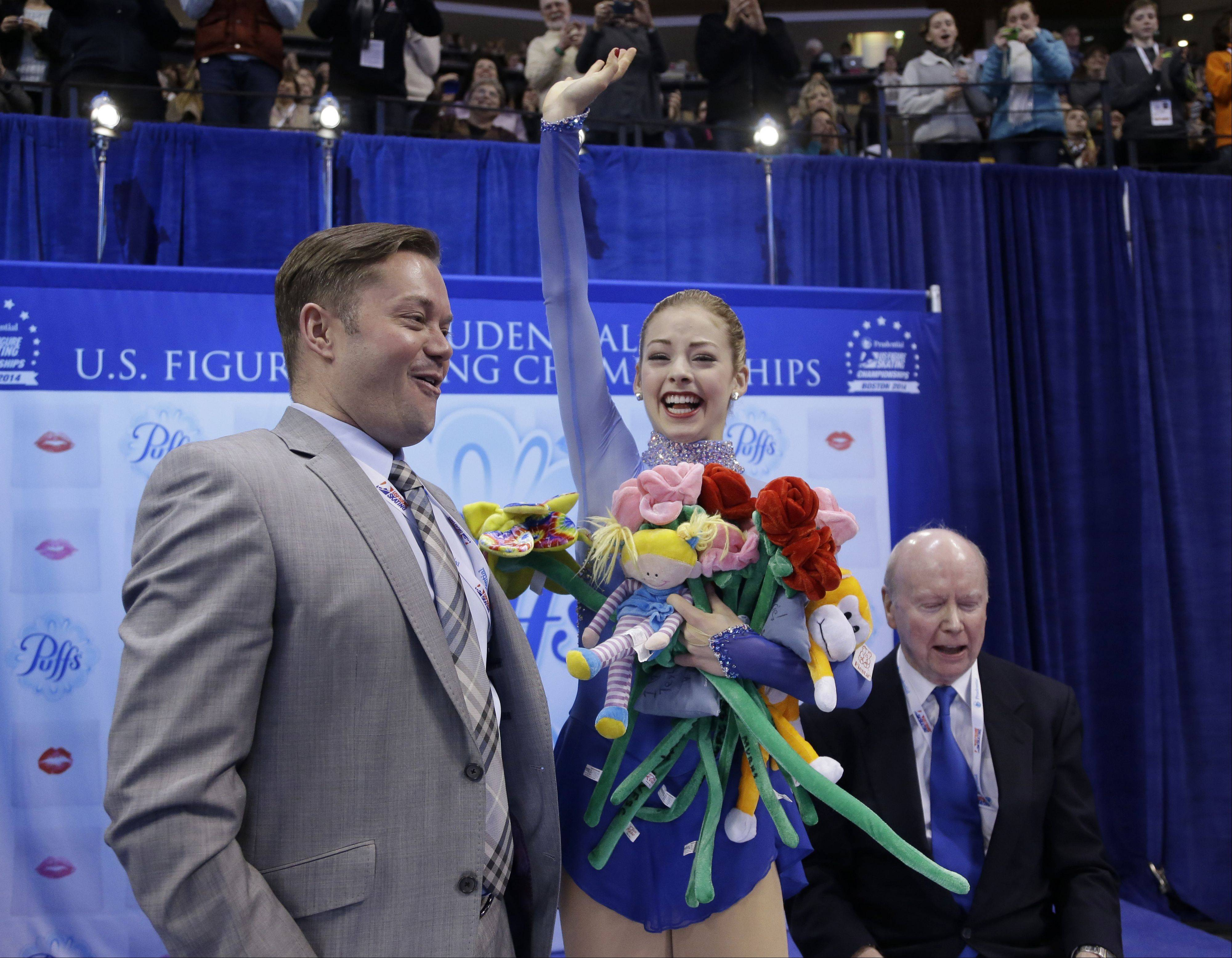 Gracie Gold celebrates as she learns her scores for the women's free skate with her coaches Scott Brown, left, and Frank Carroll, right, at the U.S. Figure Skating Championships Jan. 11 in Boston.