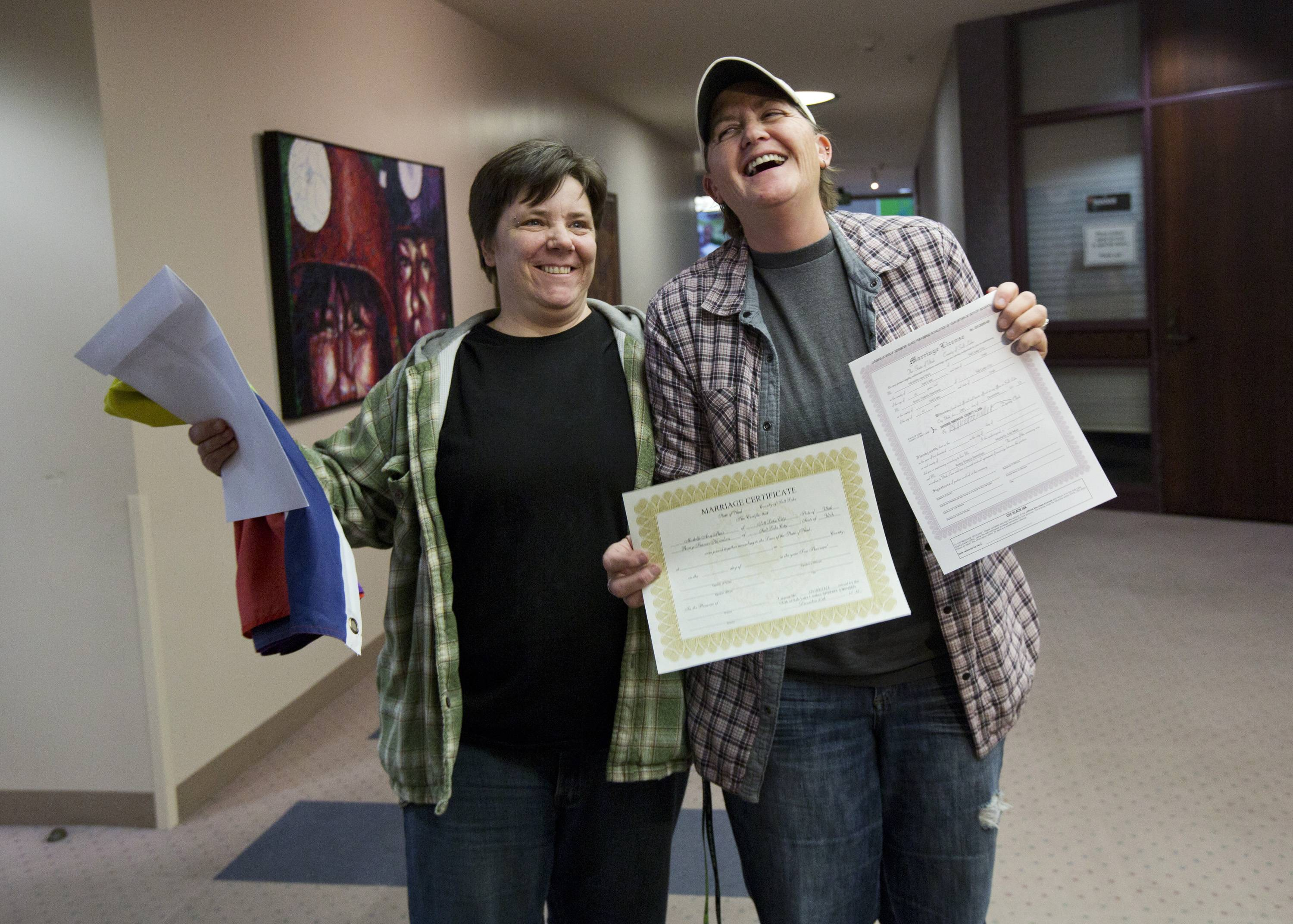 Elise Larsen, left, and Samantha Christensen, right, show off their marriage license after being one of the first same sex couples to receive one at the Salt Lake County Clerk's Office in Salt Lake City, Utah.