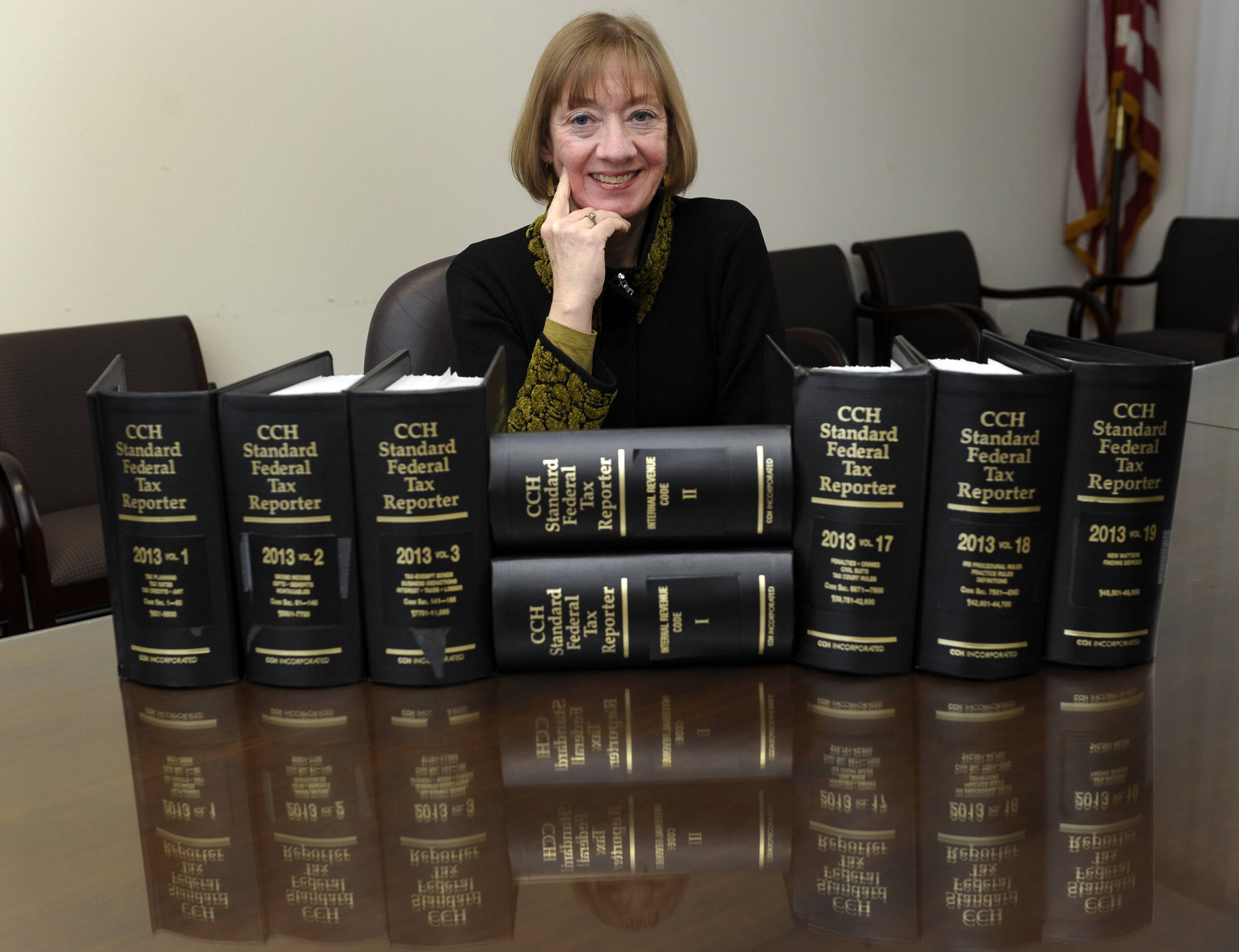 "National Taxpayer Advocate Nina Olson poses with tax code books at the Internal Revenue Service in Washington. Olson says it's not too early to start thinking about the tax implications of health care reform. ""We have an opportunity in the 2014 filing season to educate taxpayers about what they need to do during the year to avoid problems during the 2015 filing season,"" Olson said in a wide-ranging interview."