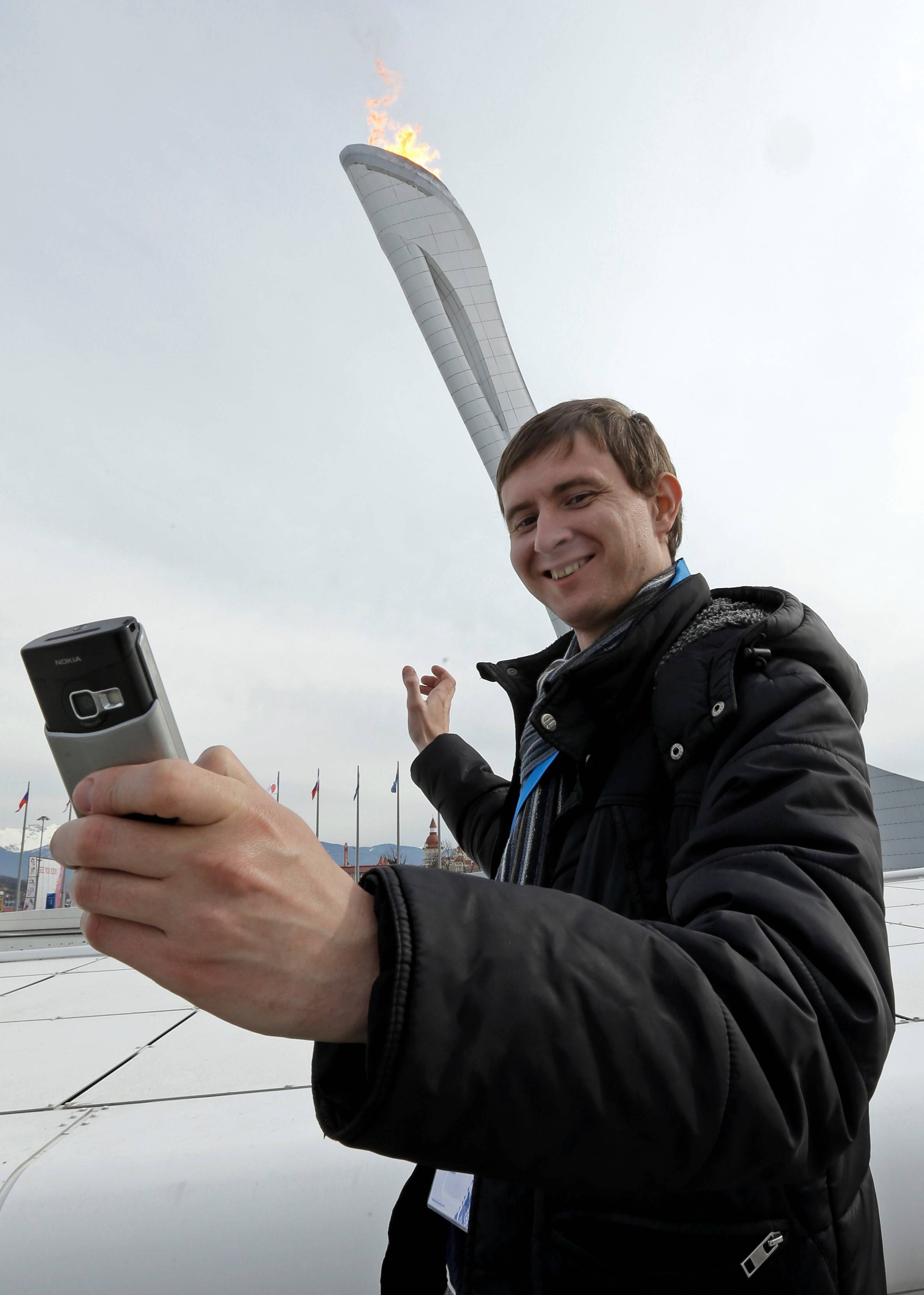 Sartakov Pavel Albertovich takes a selfie in front of the Olympic Cauldron at the 2014 Winter Olympics on Sunday in Sochi, Russia.