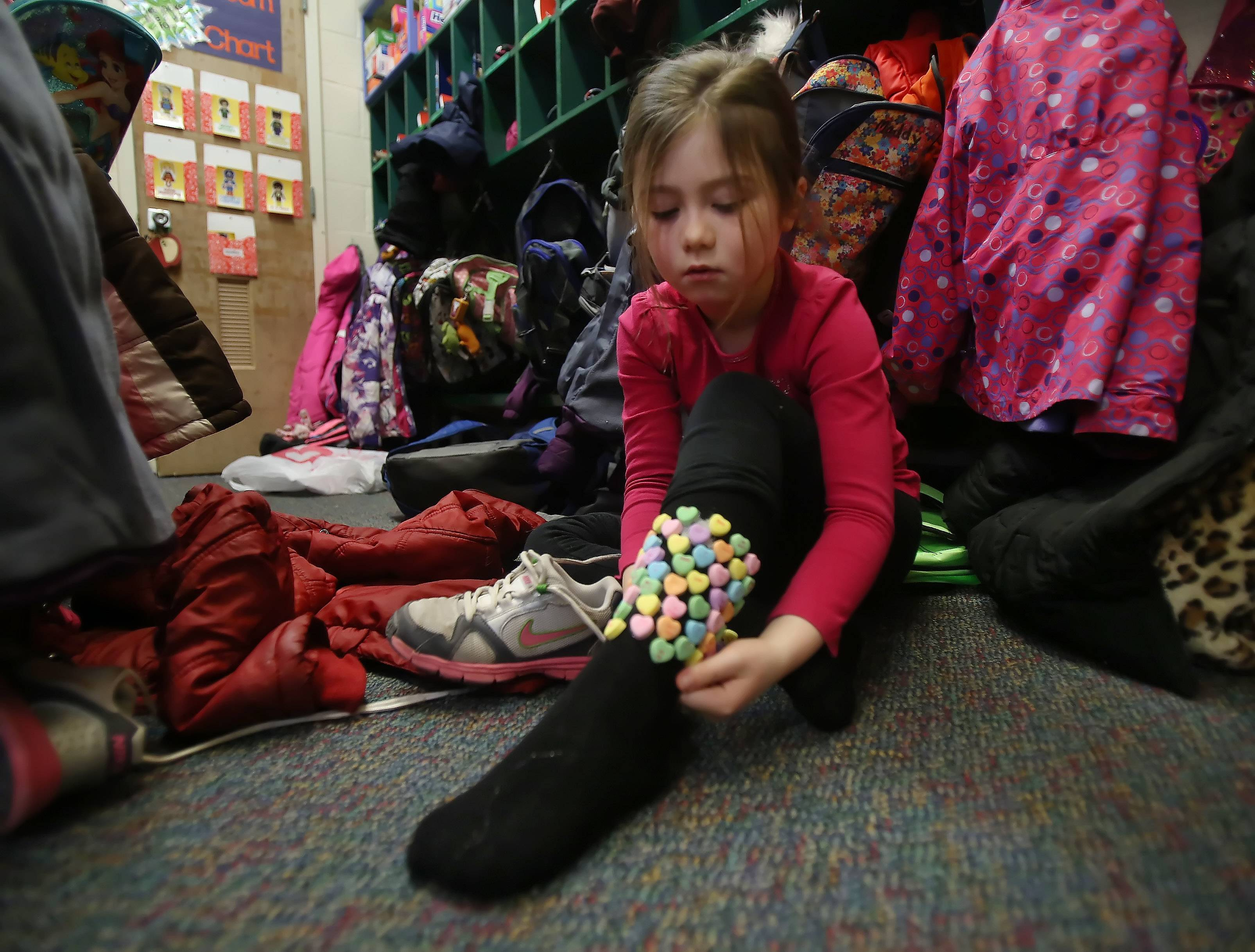 Copeland Manor School first-grader Sydney McGrath fixes her socks where she attached 100 candy hearts as students celebrate 100 days of school Tuesday in Libertyville. The students participated in various activities involving 100, including games, exercises, written and art projects.