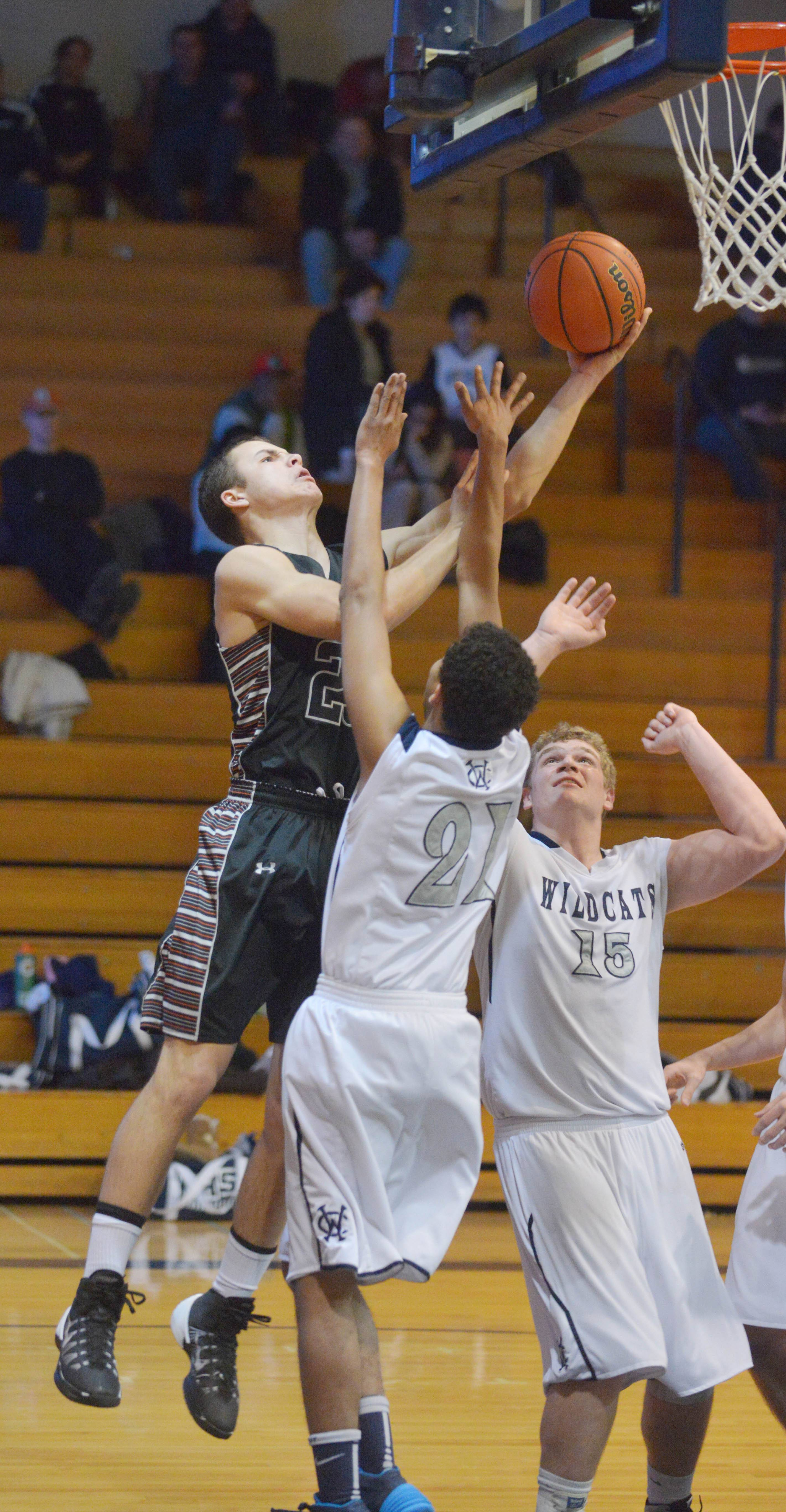 of Kaneland Tyler Carlson takes a shot over (21) Michael Bibbs and (15) Ethan Doell of West Chicago during the Kaneland at West Chicago boys basketball game Tuesday.